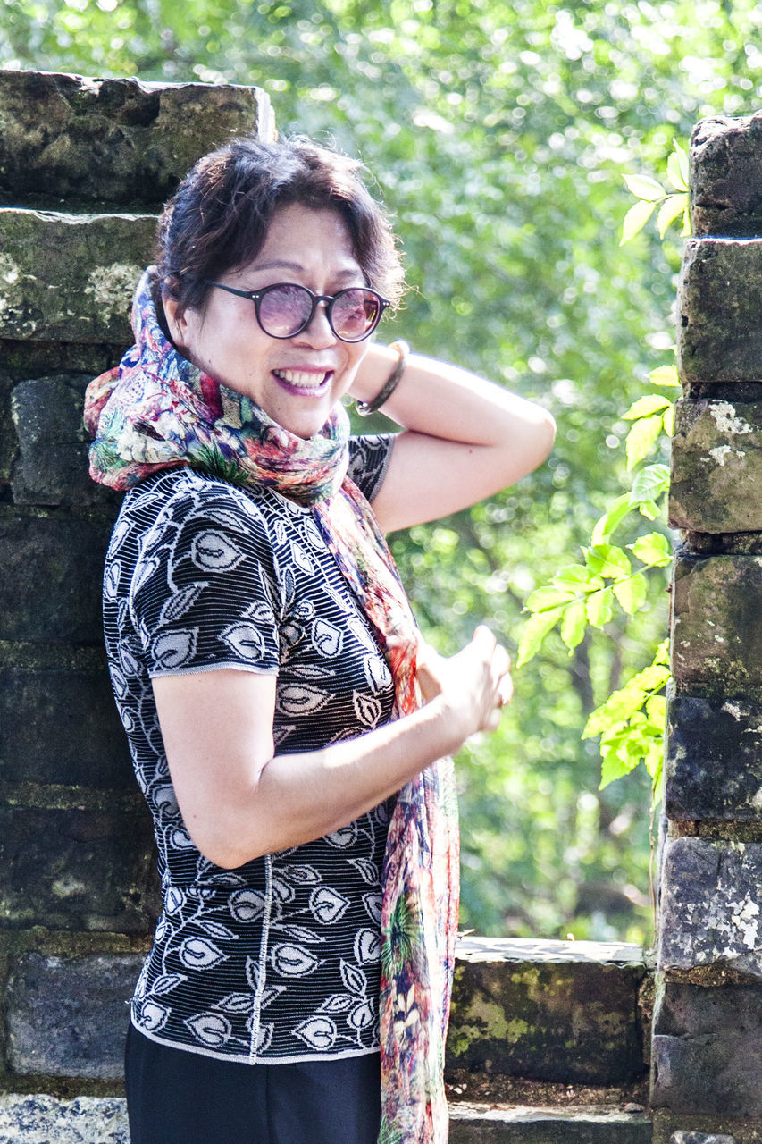 real people, leisure activity, young women, smiling, young adult, lifestyles, one person, mid adult women, outdoors, standing, day, happiness, mid adult, casual clothing, beautiful woman, looking at camera, front view, tree, eyeglasses, medium-length hair, portrait, photography themes, technology, nature