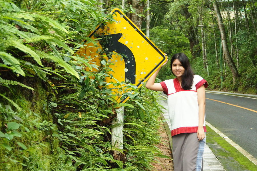 Adult Black Hair Casual Clothing Childhood Day Flower Full Length Holding Nature One Girl Only One Person Outdoors People Plant Real People Road Sign Smiling Standing Tree Turn Left Yellow Young Adult