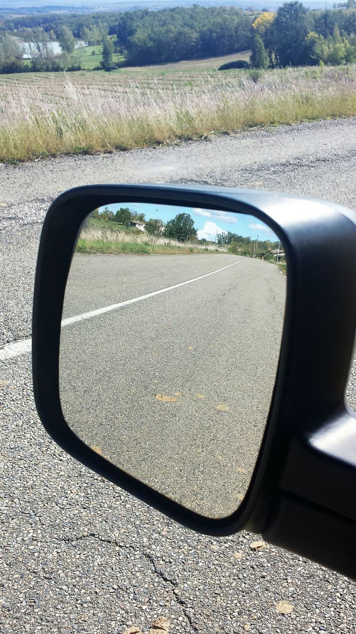 side-view mirror, car, reflection, transportation, day, sunlight, land vehicle, no people, road, nature, outdoors, close-up, water, sky