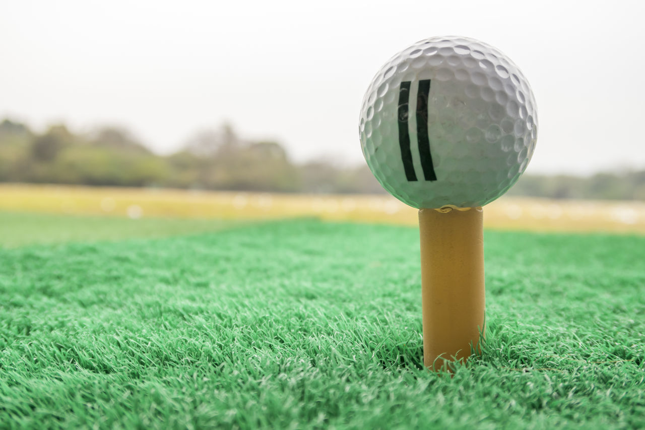 A golf ball on a plastic tee in a driving range American Football Field Ball Close-up Competition Competitive Sport Day Drink Golf Golf Course Grass Green - Golf Course Green Color Nature No People Outdoors Playing Field Sky Soccer Field Sport Taking A Shot - Sport Tee