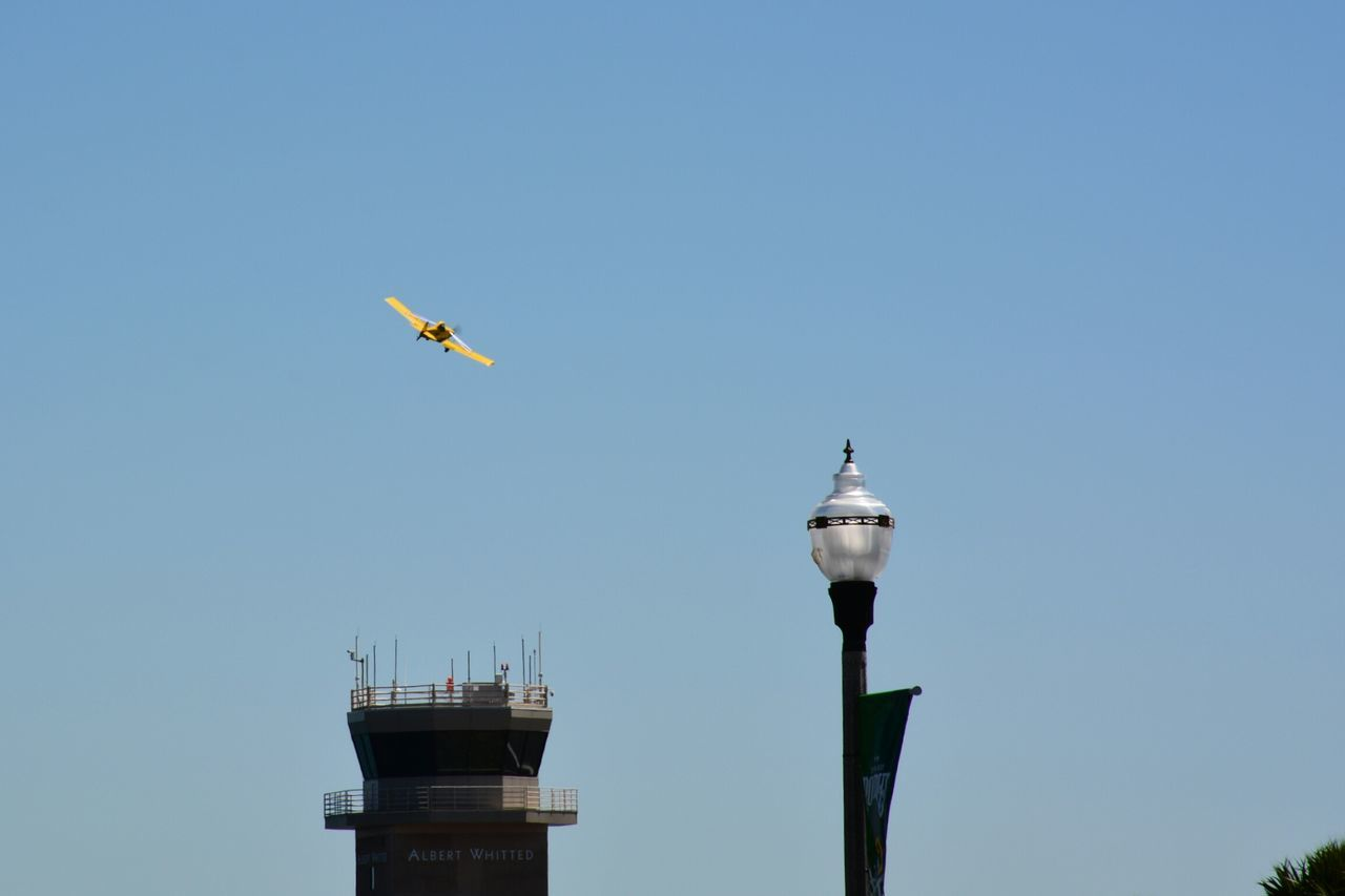 yellow airplane passing by airport tower Sky Blue Clear Sky Outdoors Flying Day Low Angle View No People Airport Tower Airport Airplane Yellow Color Yellow Transportation