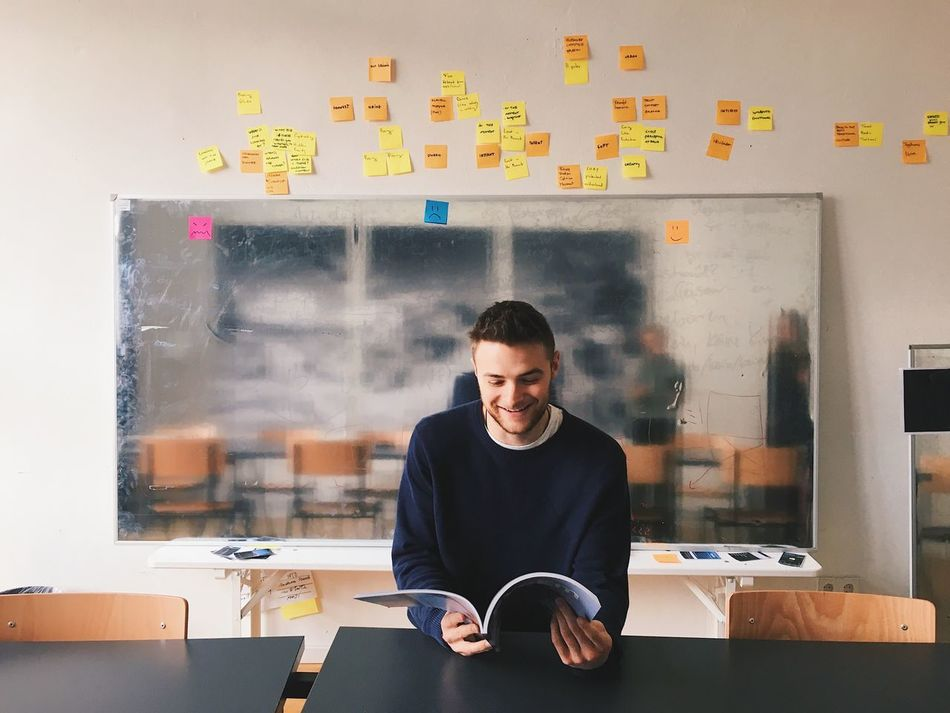 One Man Only Creativity Casual Clothing Sitting Young Adult Concentration Looking Front View Reading Smiling Office Startup