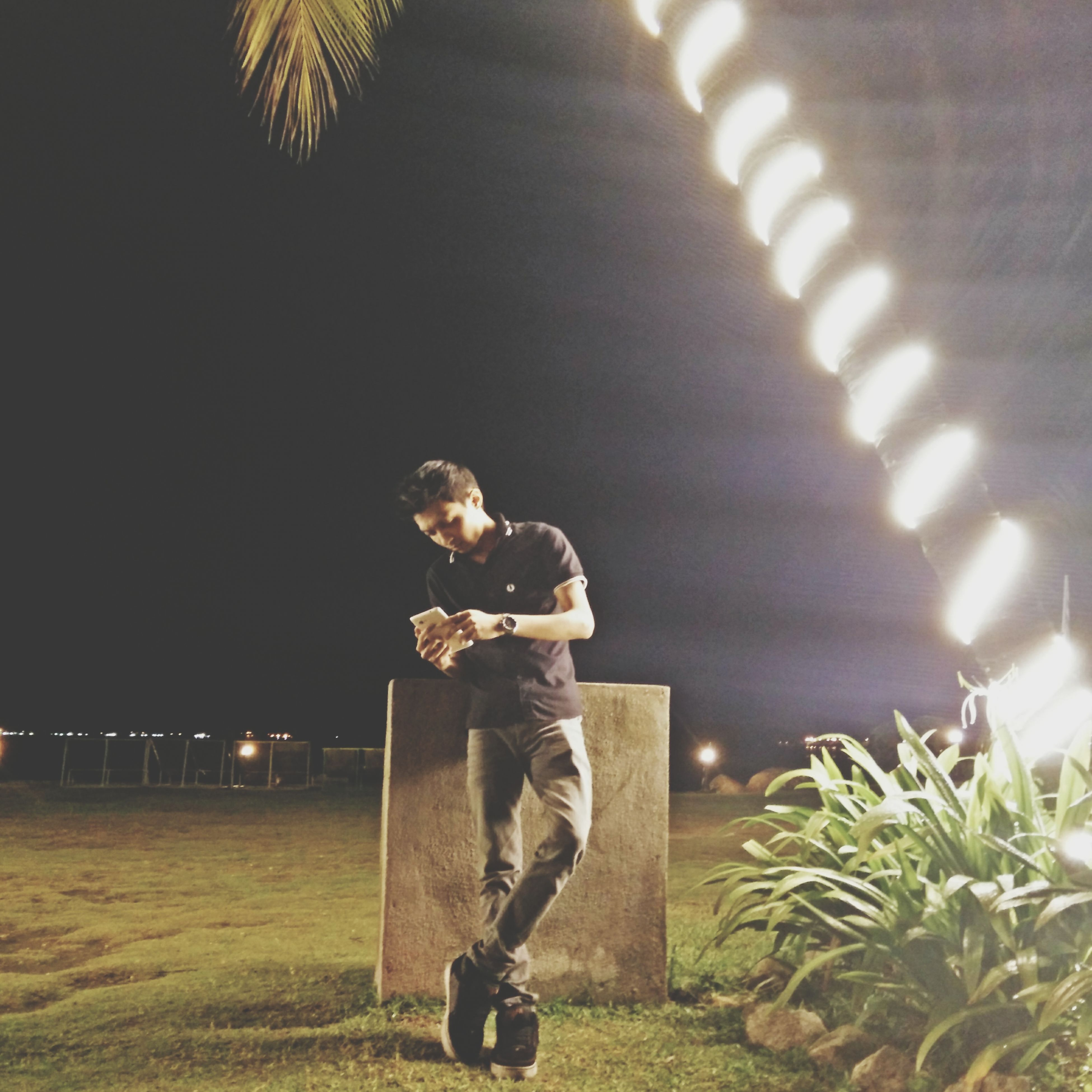 night, lifestyles, illuminated, leisure activity, full length, standing, men, casual clothing, rear view, arts culture and entertainment, holding, lighting equipment, person, boys, three quarter length, playing, childhood, outdoors