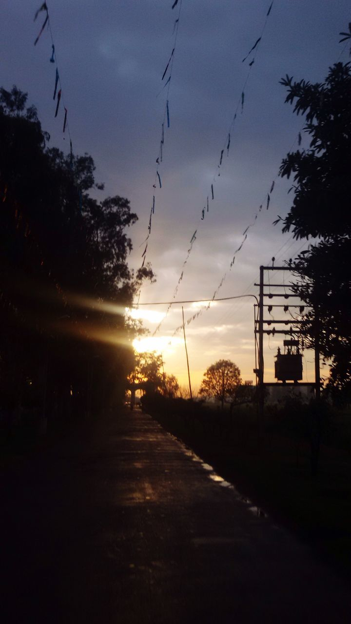Silhouette Of Trees By Railroad Station Platform Against Sky At Sunset