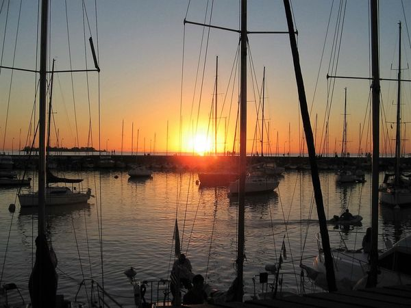 The sun going down behind the breakwater at the Yachting Club on the River Plate in Colonia del Sacramento, Uruguay. Beauty In Nature Breakwater Colonia Del Sacramento - Uruguay Day Mast Nature Nautical Vessel Outdoors Red Sunset Reflection River Plate Sailing Sailors Scenics Sea Silhouette Sky Sun Sunset Tourism Tourist Attraction  Tranquility Water Yacht