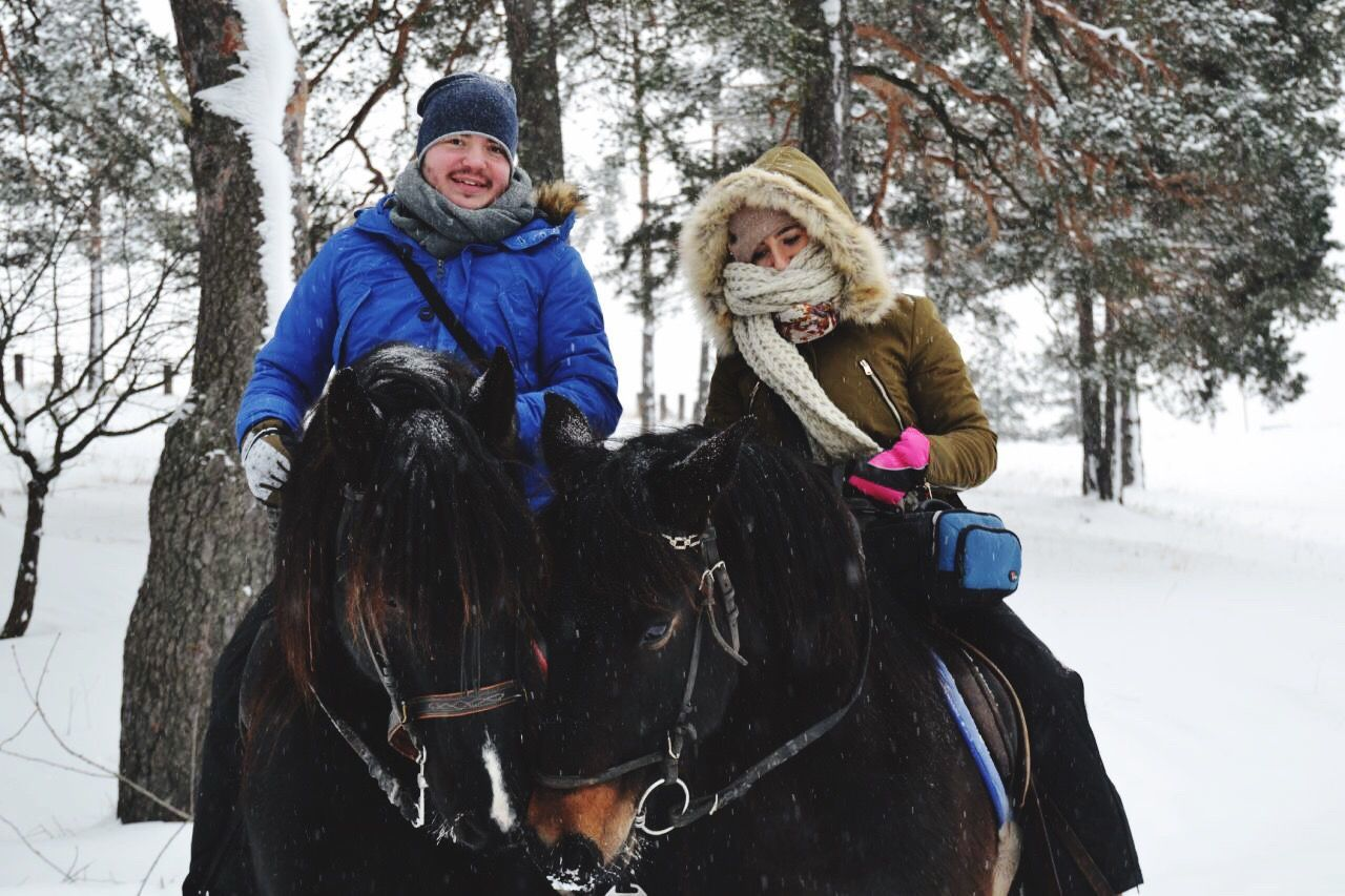 snow, winter, cold temperature, domestic animals, warm clothing, togetherness, animal themes, two people, riding, mammal, outdoors, happiness, day, leisure activity, tree, smiling, real people, nature
