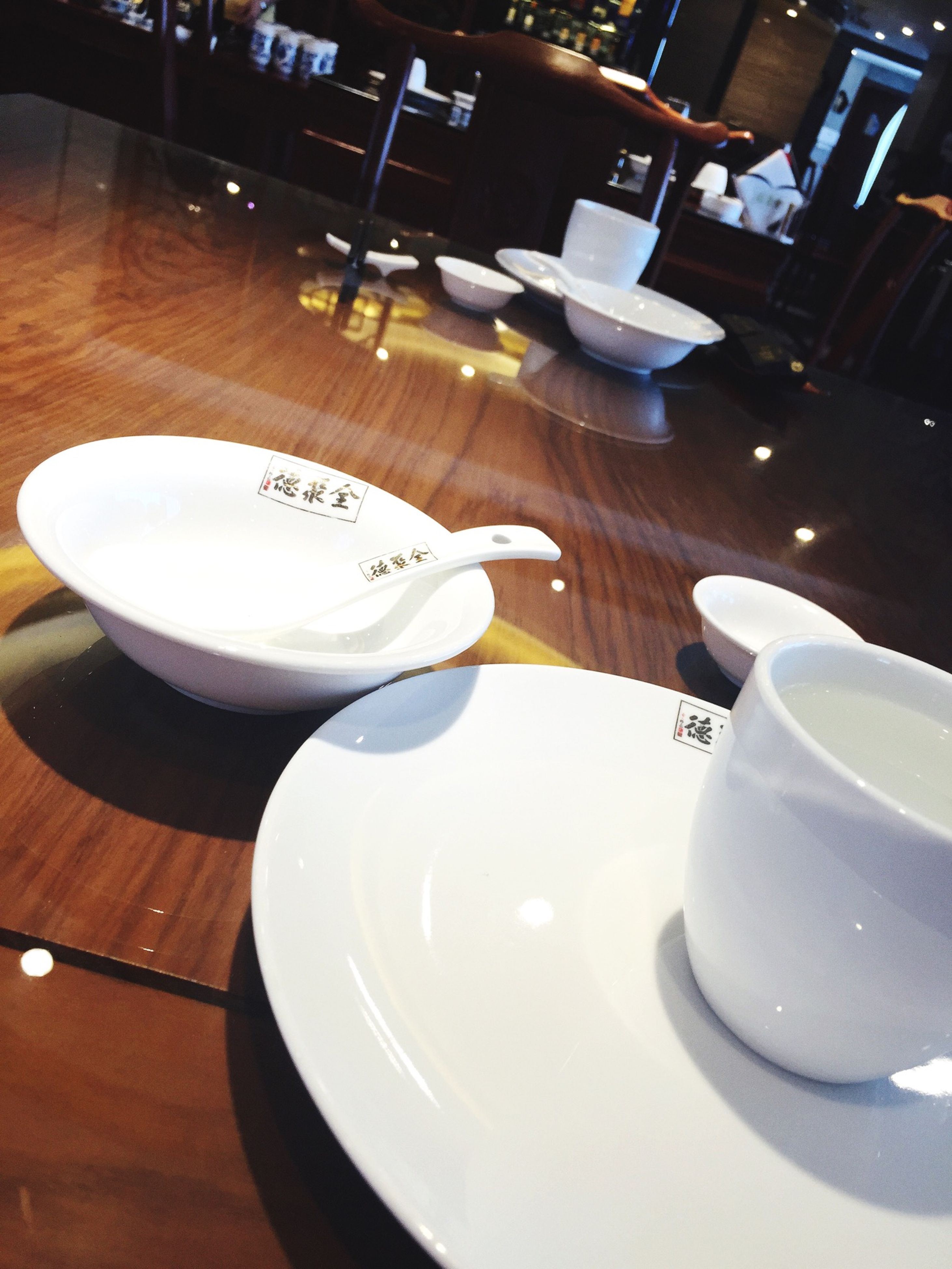 indoors, table, plate, still life, chair, high angle view, spoon, coffee cup, white color, empty, drink, food and drink, absence, restaurant, saucer, no people, fork, cup, refreshment, reflection