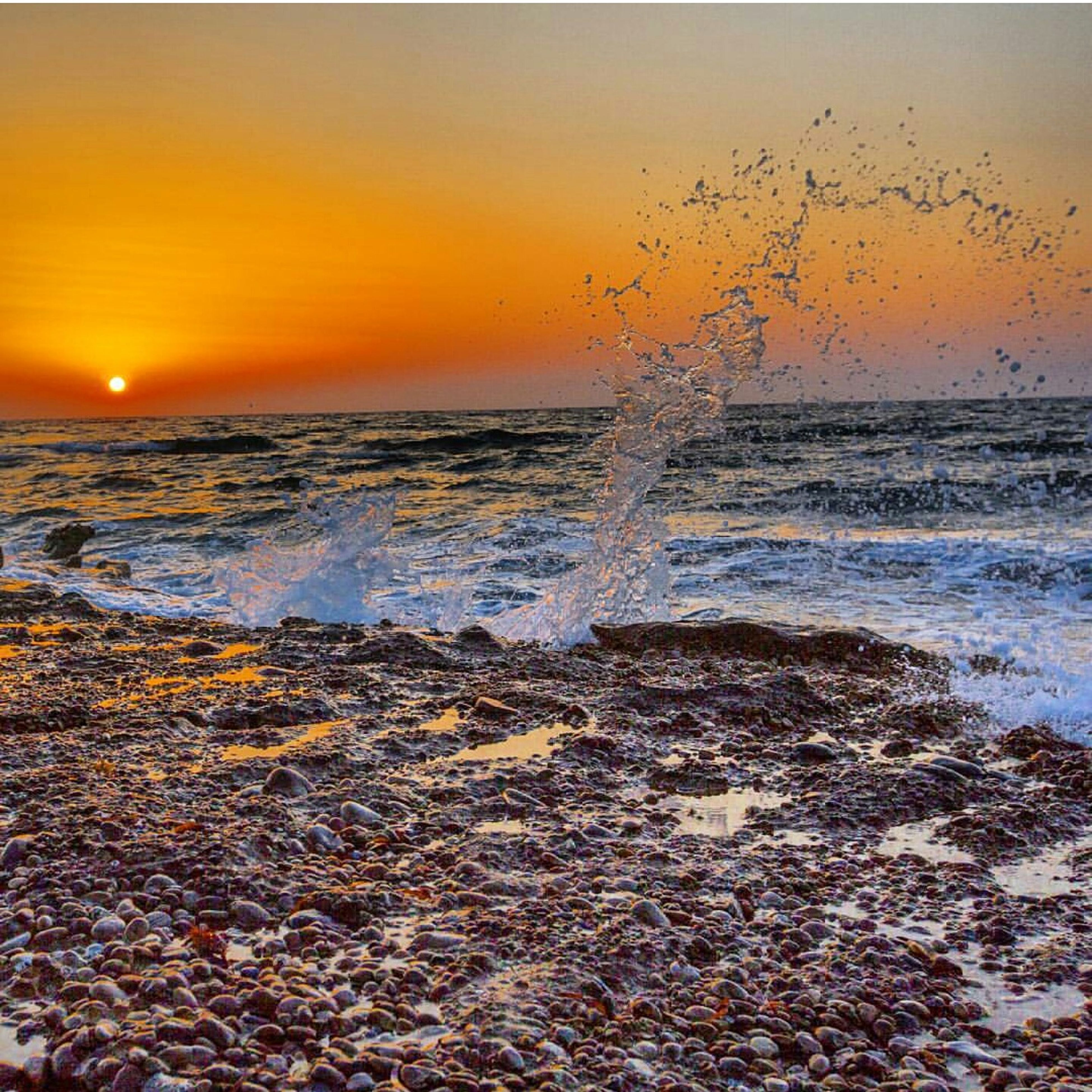 sunset, sea, motion, water, wave, horizon over water, splashing, orange color, sun, scenics, power in nature, beach, nature, beauty in nature, surf, non-urban scene, sky, majestic, shore, waterfront, outdoors, vacations, tranquility, seascape, atmospheric mood, tranquil scene