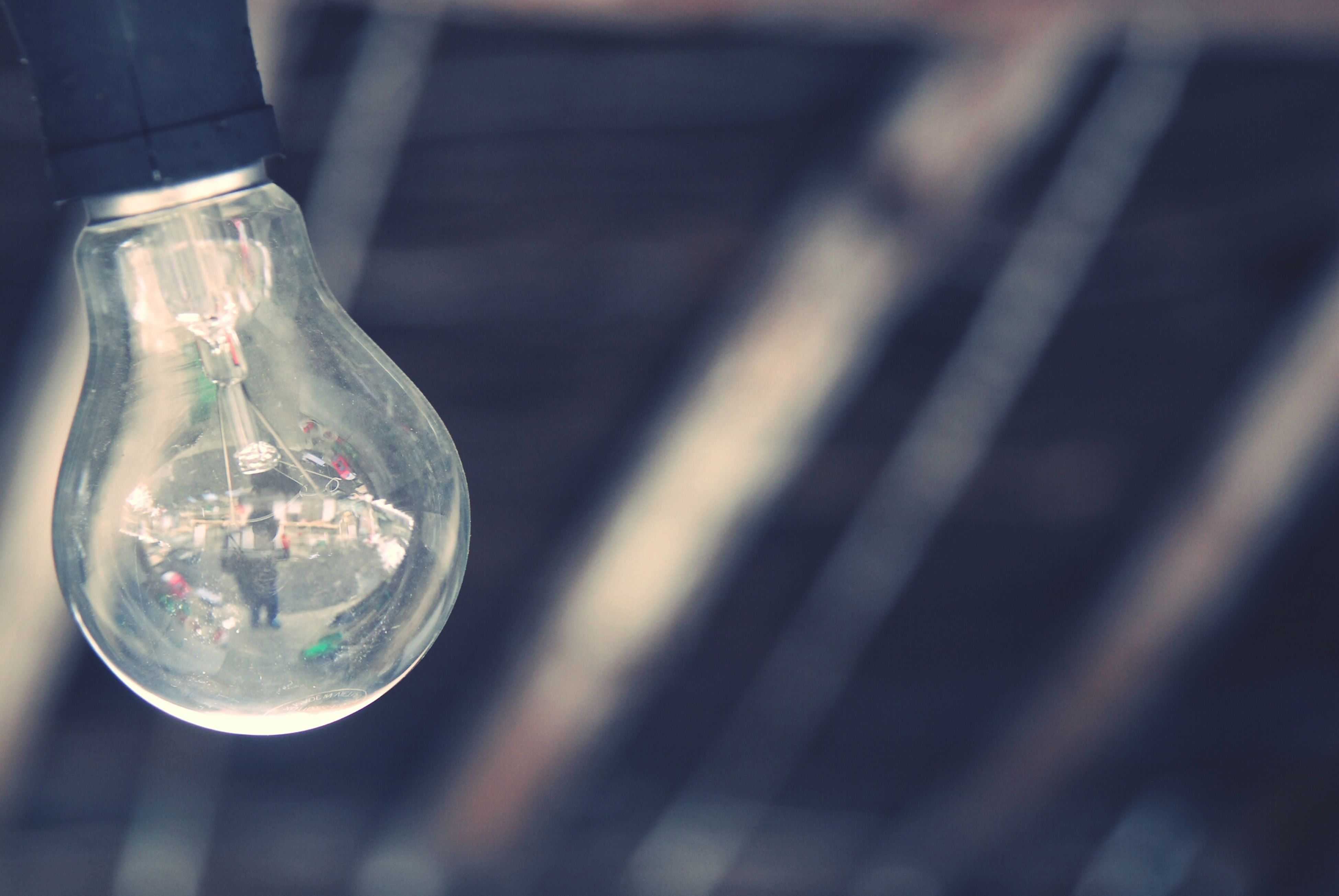indoors, focus on foreground, close-up, glass - material, lighting equipment, transparent, illuminated, light bulb, hanging, selective focus, shiny, reflection, no people, decoration, still life, metal, glass, fragility, electricity, electric light