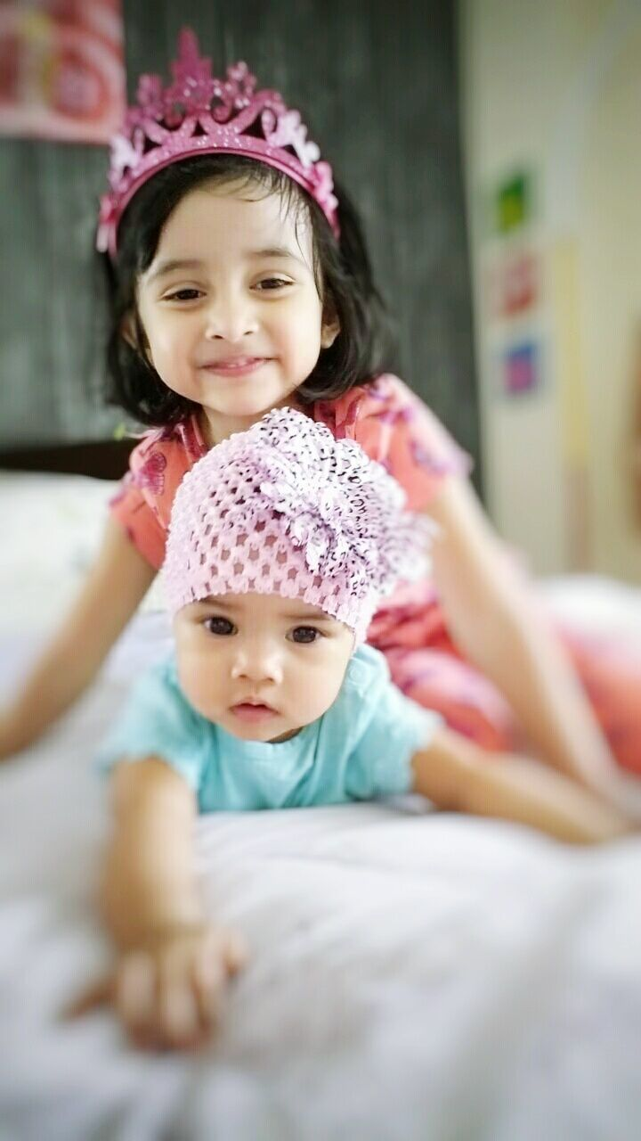 baby, looking at camera, innocence, childhood, togetherness, cute, family with one child, selective focus, love, portrait, real people, happiness, smiling, bed, indoors, babyhood, bonding, daughter, care, lifestyles, day, crown, close-up, people, adult