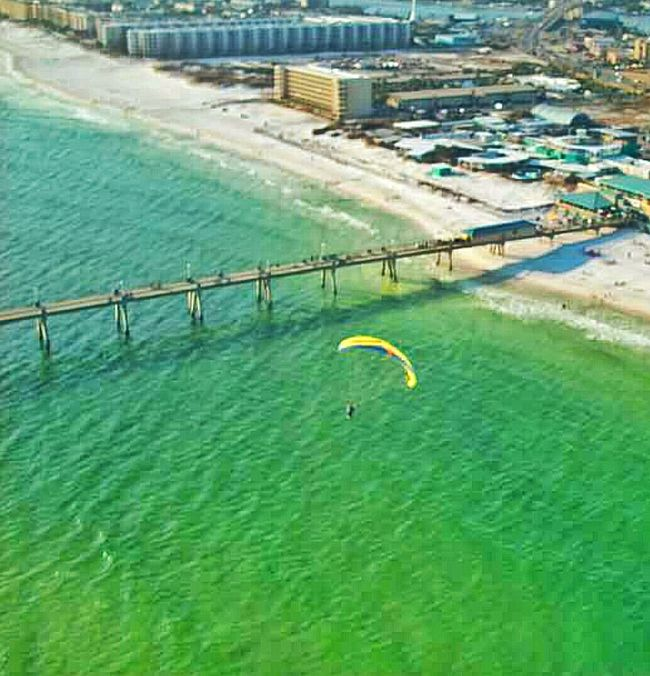 Parasailing Yellow Parachute View From Above Beach Life Bridge Buildings Outdoor Sports Outdoor Activities Daredevil Sky View View From The Top Beach Photography People On The Beach Florida Bay Bridge Bridge Over Ocean Green Water Air Sports Long Bridge The Essence Of Summer People Of The Oceans Fort Walton Beach Florida, Usa. people love doing this but I'm too afraid to try it. A Birds Eye View