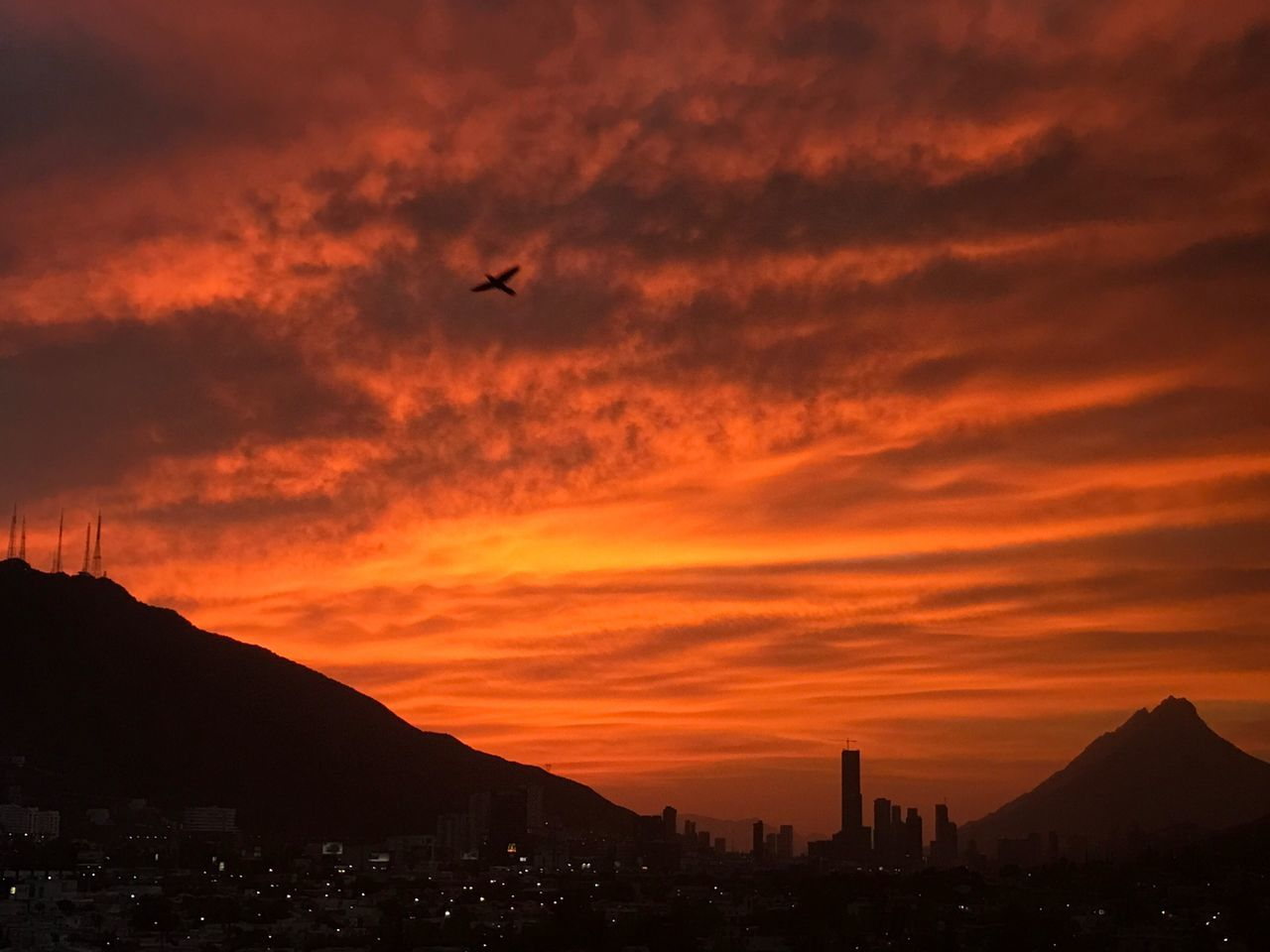sunset, silhouette, flying, sky, building exterior, architecture, built structure, nature, mountain, cloud - sky, no people, outdoors, animal themes, bird, beauty in nature, cityscape, mid-air, one animal, city, scenics, animals in the wild, skyscraper, spread wings, day