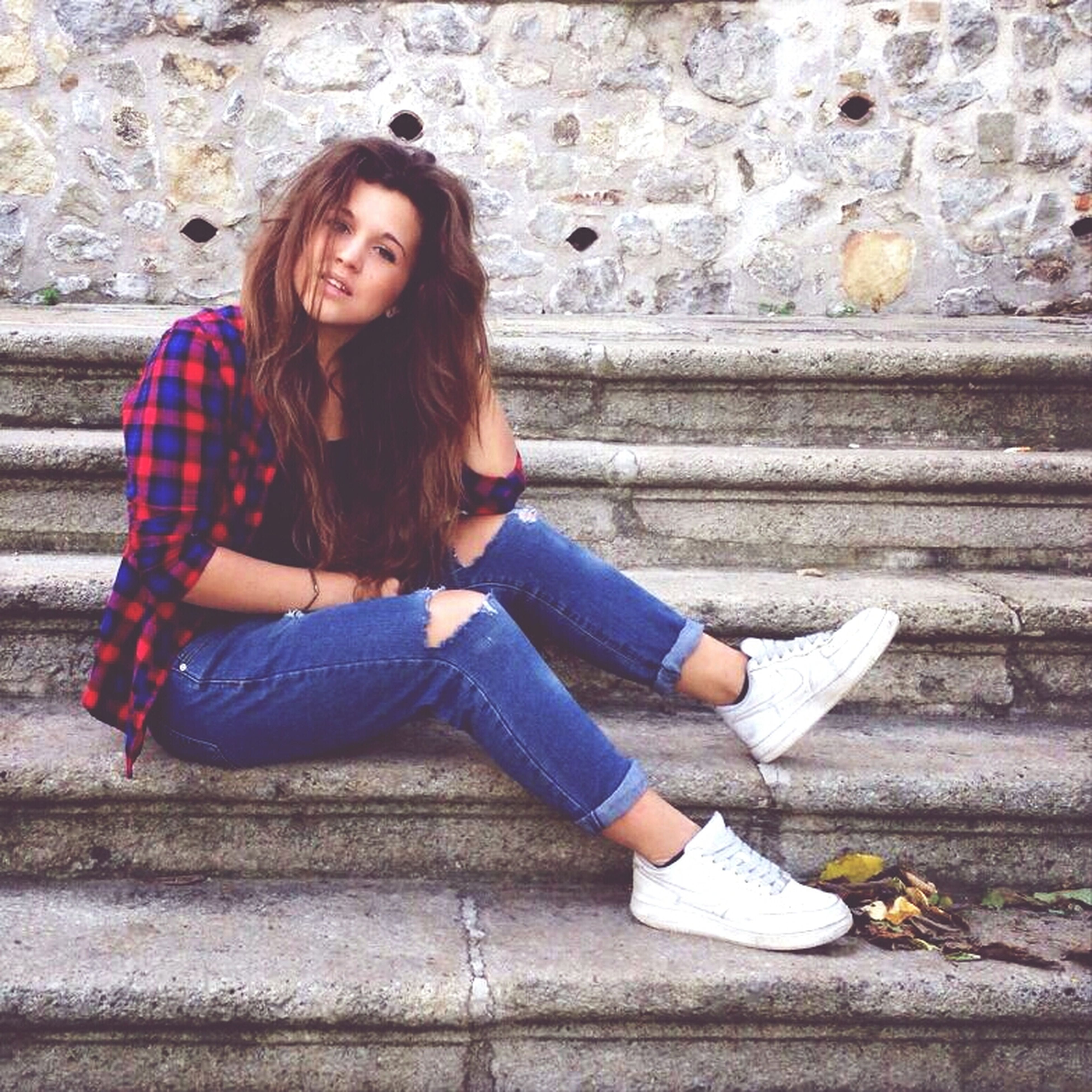 person, young adult, casual clothing, lifestyles, young women, full length, sitting, leisure activity, portrait, looking at camera, three quarter length, front view, standing, smiling, wall - building feature, long hair, happiness