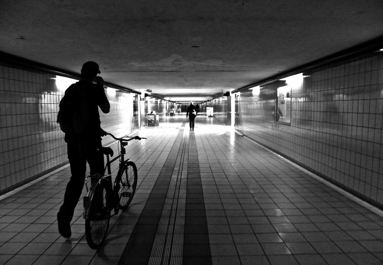 bicycle, real people, transportation, full length, the way forward, walking, lifestyles, built structure, architecture, men, cycling, city life, illuminated, women, indoors, two people, day, commuter, walkway, adult, people