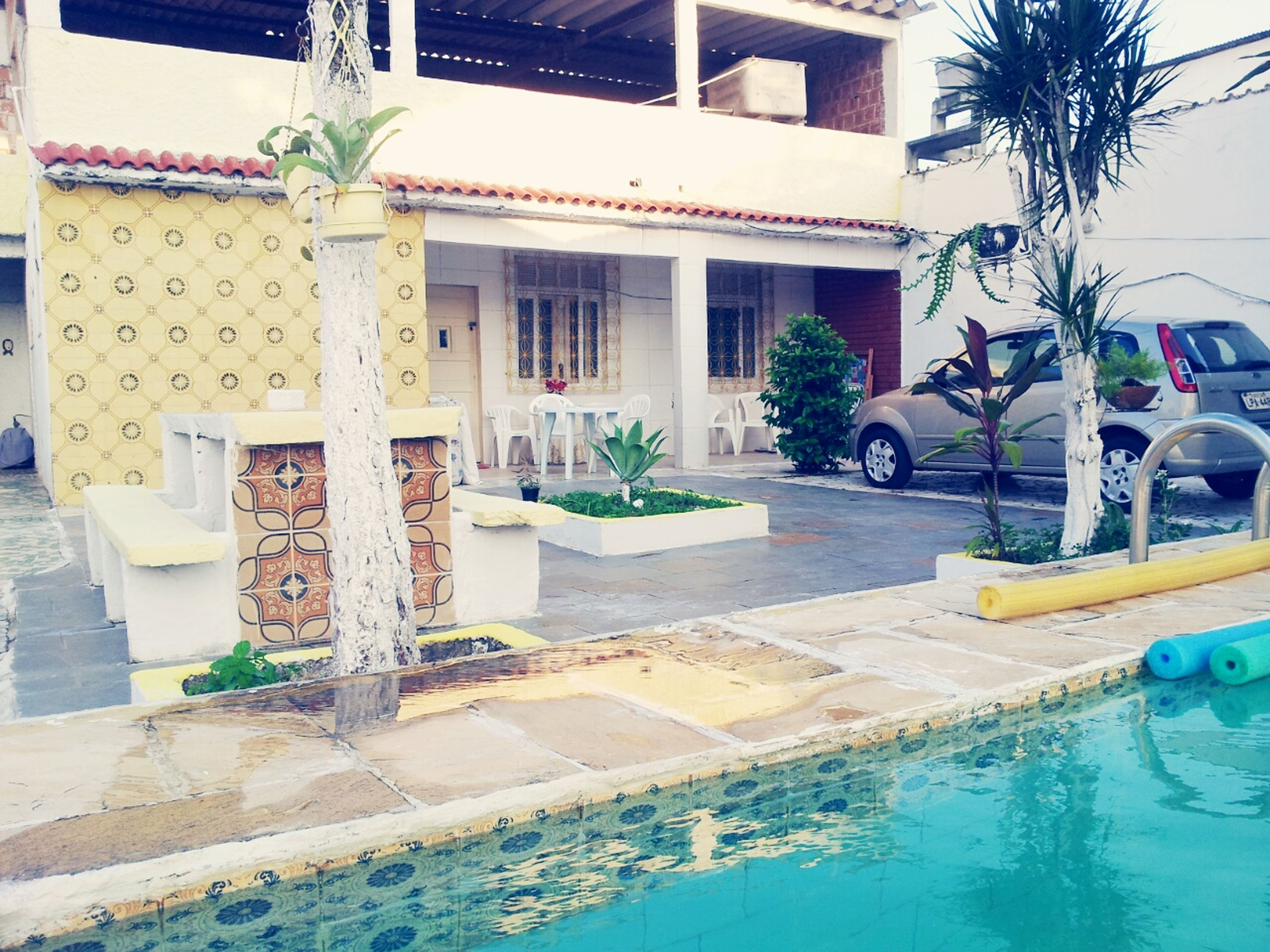 building exterior, architecture, built structure, house, residential building, residential structure, tree, palm tree, city, building, potted plant, window, street, sidewalk, swimming pool, sunlight, day, outdoors, balcony, incidental people