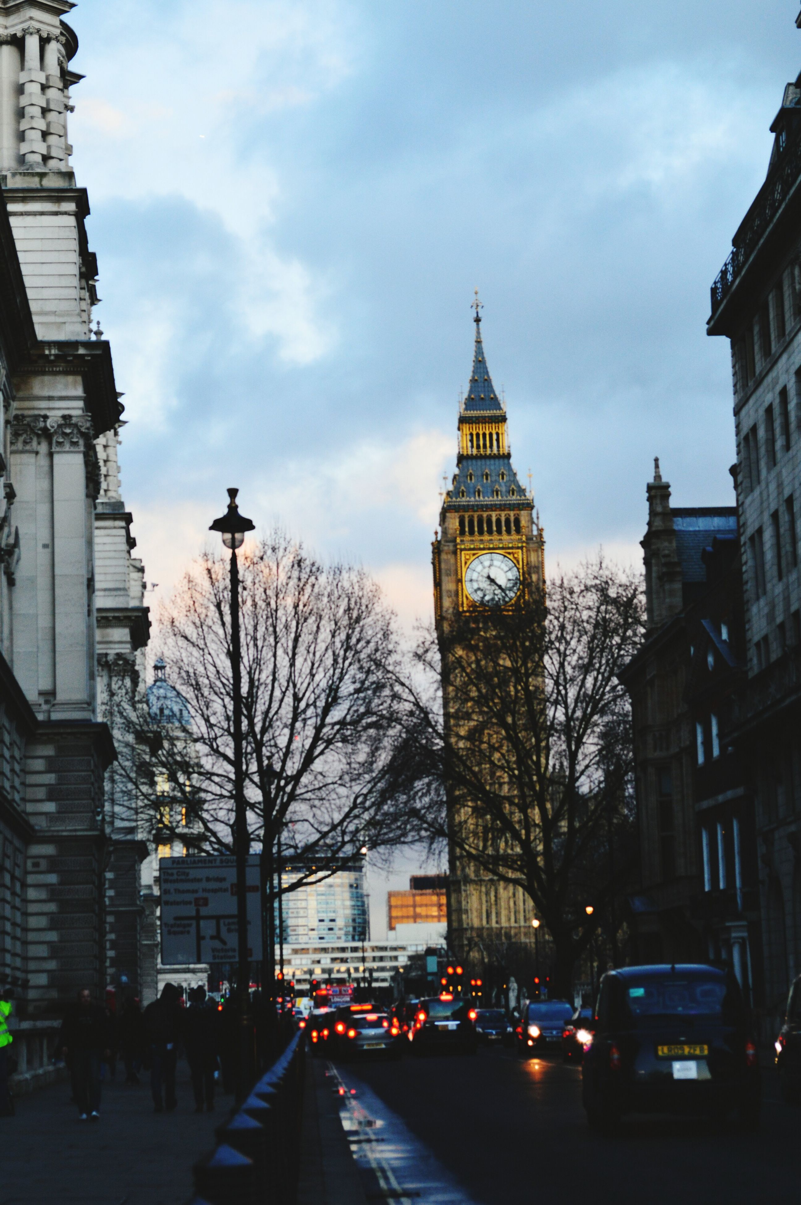 architecture, building exterior, built structure, city, street, car, sky, tower, transportation, city life, land vehicle, city street, road, travel destinations, tall - high, capital cities, clock tower, travel, famous place, incidental people