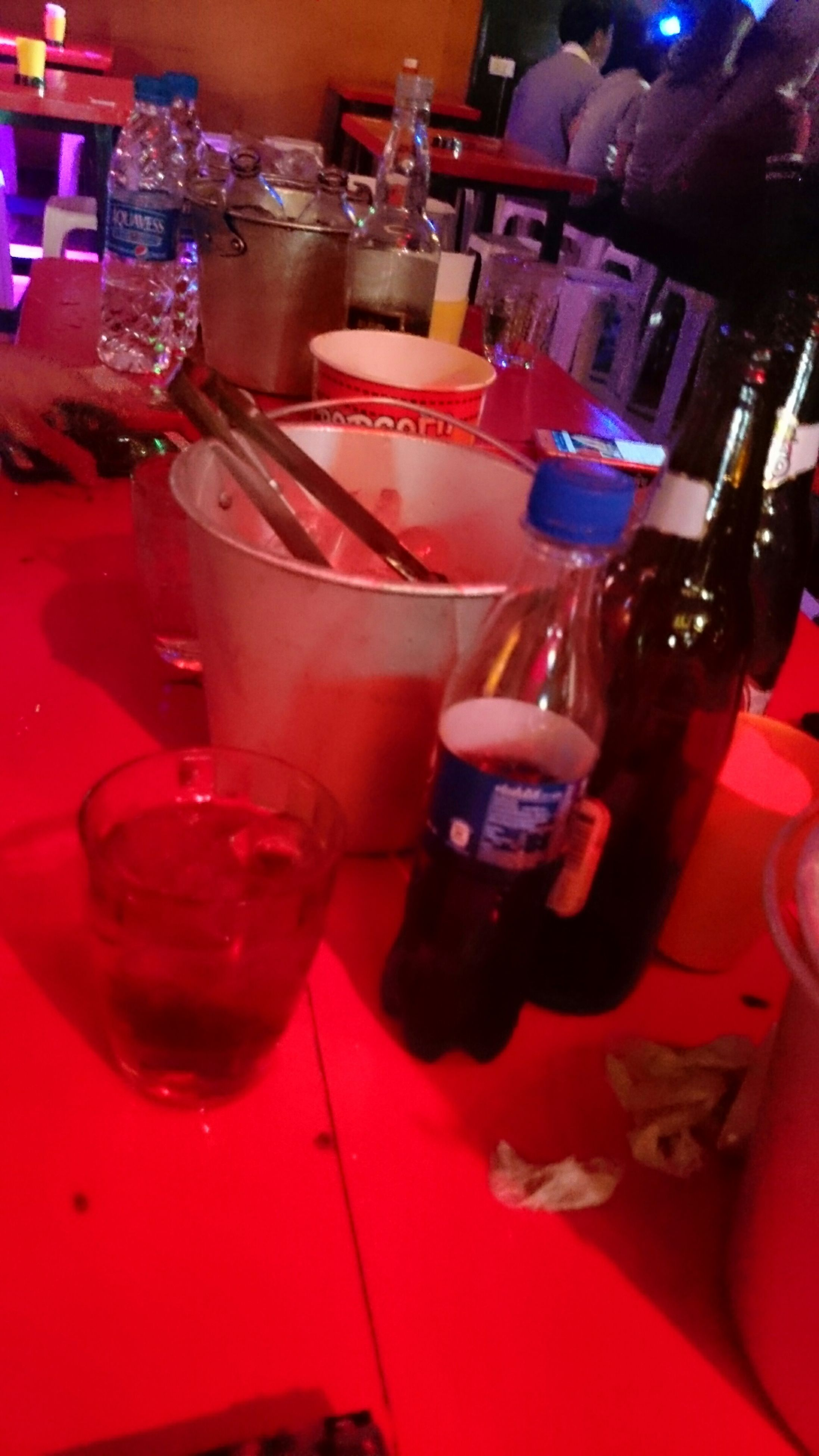 indoors, table, drinking glass, illuminated, drink, red, restaurant, wineglass, refreshment, glass - material, bottle, arts culture and entertainment, alcohol, still life, person, close-up, leisure activity, food and drink, home interior