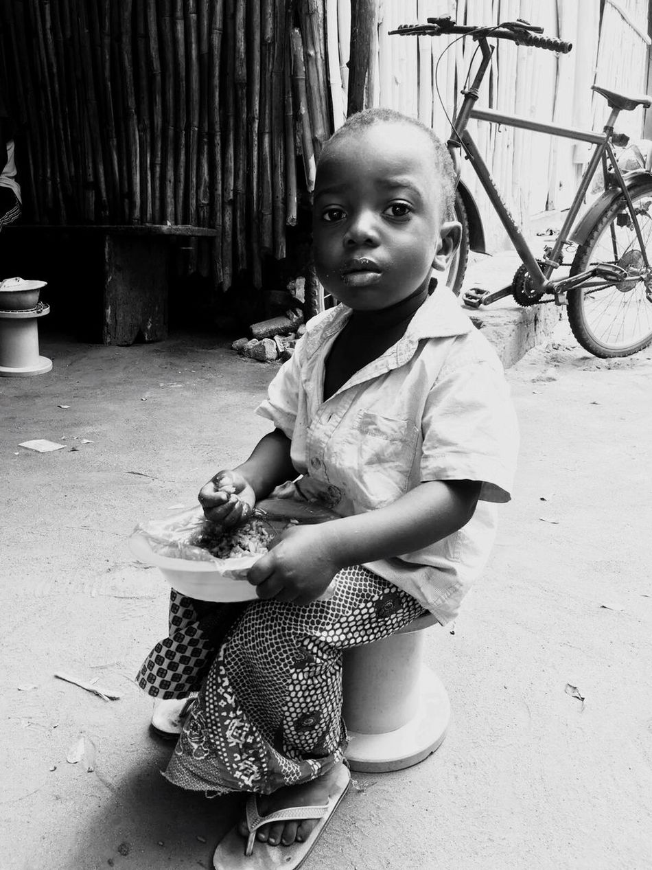 EyeEmNewHere One Person Sitting Childhood Lifestyles Full Length Outdoors Real People Baby Portrait Day Togo Africa Bike Food Child Cute Girl Pink Outside Nature Mobile Conversations Break The Mold