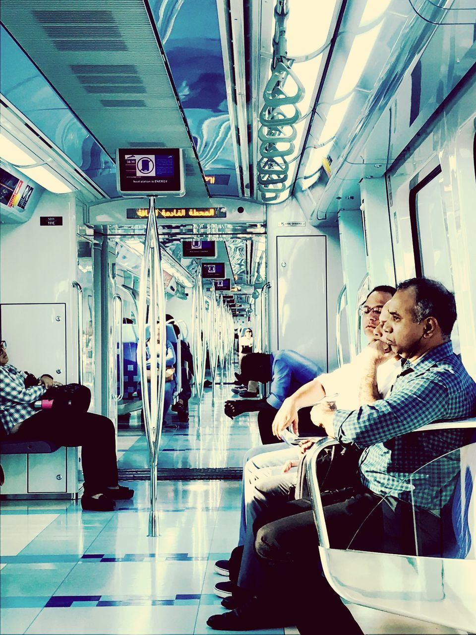 two people, transportation, indoors, real people, togetherness, sitting, mid adult men, men, public transportation, lifestyles, leisure activity, young adult, standing, young women, full length, vehicle seat, day, people