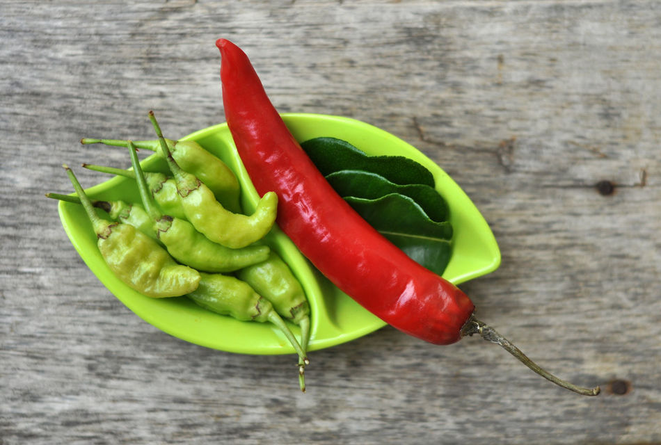 Red and Green Chili Pepper Bowl Chili Pepper Close-up Day Food Food And Drink Freshness Green Chili Pepper Green Color Green Leaf Healthy Eating High Angle View Indoors  Leaf Lime Green Lime Leaves No People Ready-to-eat Red Red Chili Red Chili Pepper Still Life Table Vegetable Wooden