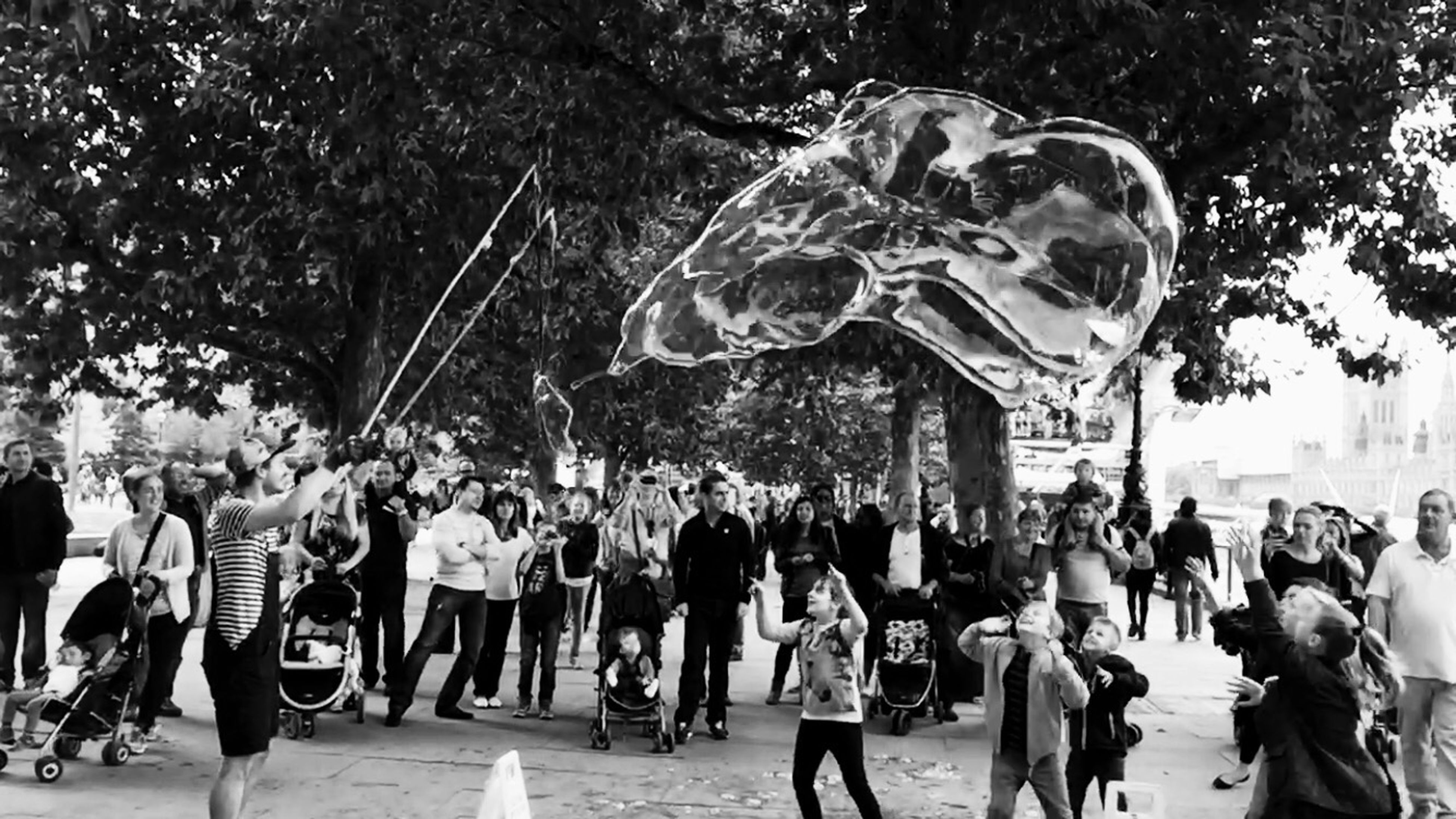 large group of people, person, men, lifestyles, leisure activity, arts culture and entertainment, crowd, mixed age range, tree, sculpture, celebration, art and craft, street, cultures, statue, built structure, motion, outdoors, travel