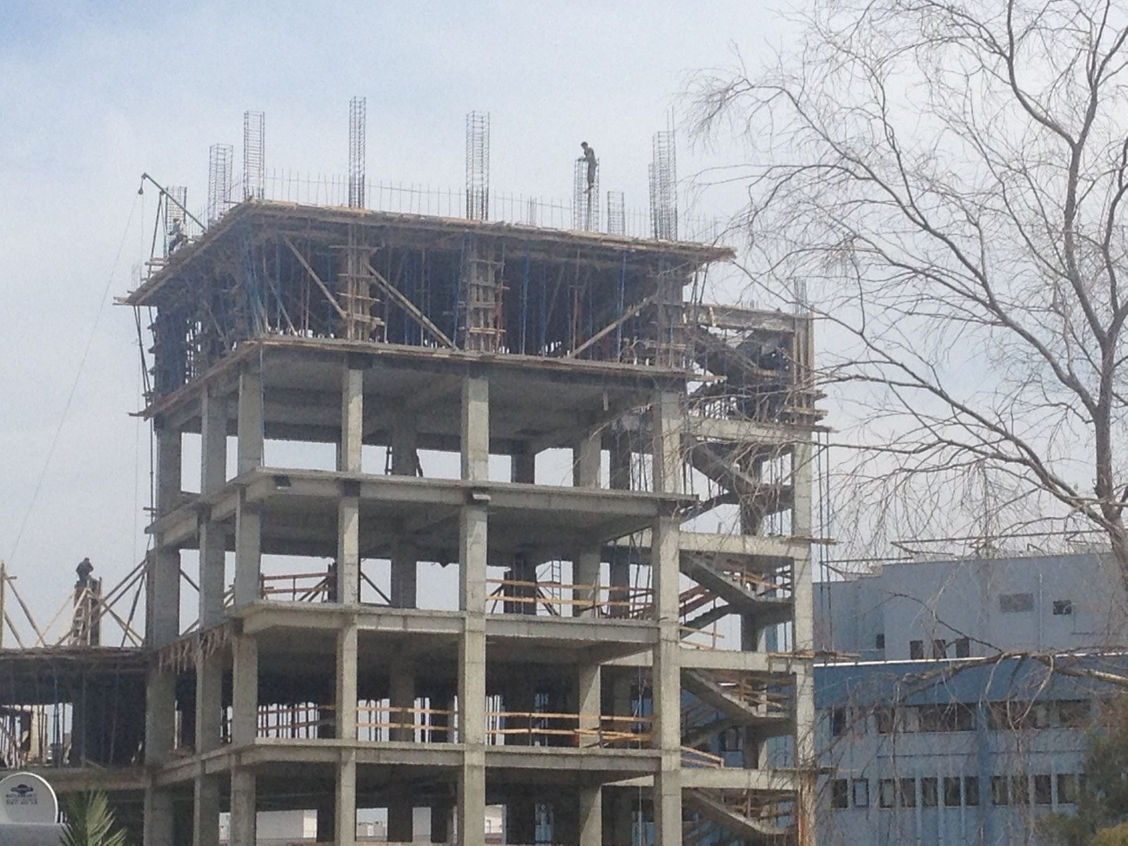 architecture, built structure, building exterior, construction site, low angle view, development, construction, industry, sky, crane - construction machinery, factory, building, incomplete, day, city, residential building, clear sky, outdoors, bare tree, no people