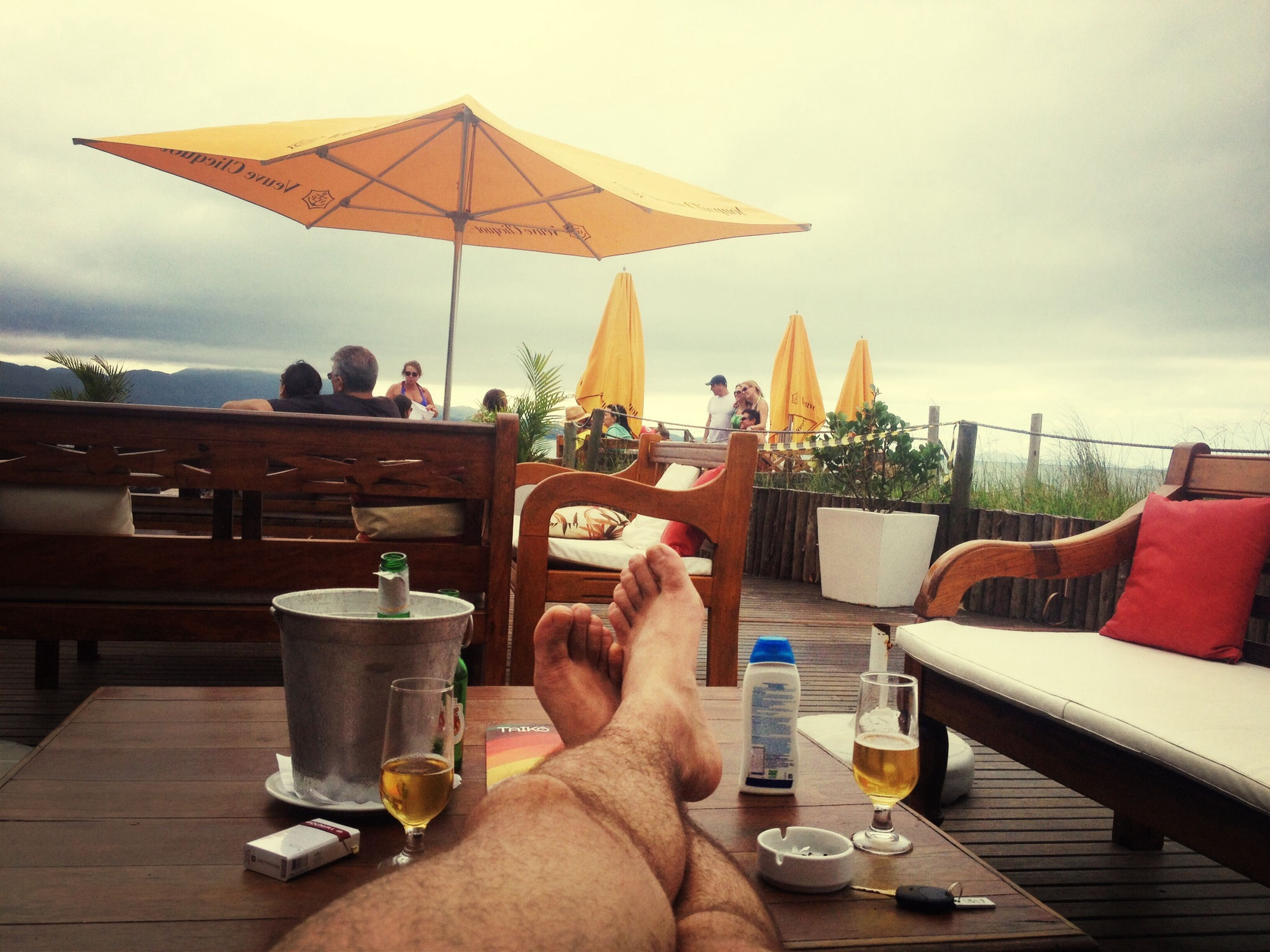 table, chair, person, drink, sky, relaxation, personal perspective, lifestyles, leisure activity, part of, cloud - sky, food and drink, sitting, unrecognizable person, men, cropped, restaurant