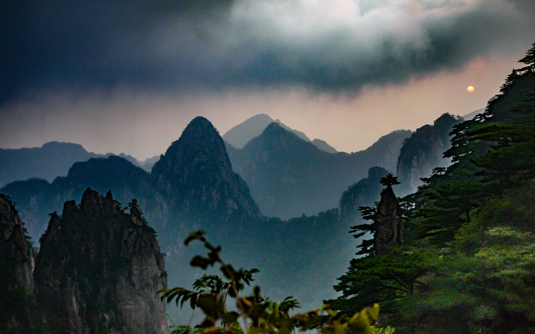 """Land of magic and people... a lot of people We decided to get up early and catch the famous sunrise over Huangshan National Park. Luckily I am a head taller than the average Chinese, so I had no difficulty to see the amazing scenery of the magical sunrise over the heads of dozens of people already there. Thank goodness the travel guides decided to sleep in, so we were not deafened by the countless megaphones blasting useless information to confirm the purpose of the tour guide and ruin the purpose of the visit. They would make up for it in the afternoon though... (Panasonic DMC-GF1 LUMIX G 20/F1.7 ƒ/1.7 20mm 1/400"""" iso 100 @25%) Adventure ASIA Beauty In Nature China Dawn Day Forest Huangshan Landscape Morning Mountain Miles Away National Park Nature Nature No People Outdoors Rural Scenics Sky Storm Cloud Sunrise Tree Yellow Mountains BEIJING北京CHINA中国BEAUTY The Great Outdoors - 2017 EyeEm Awards"""