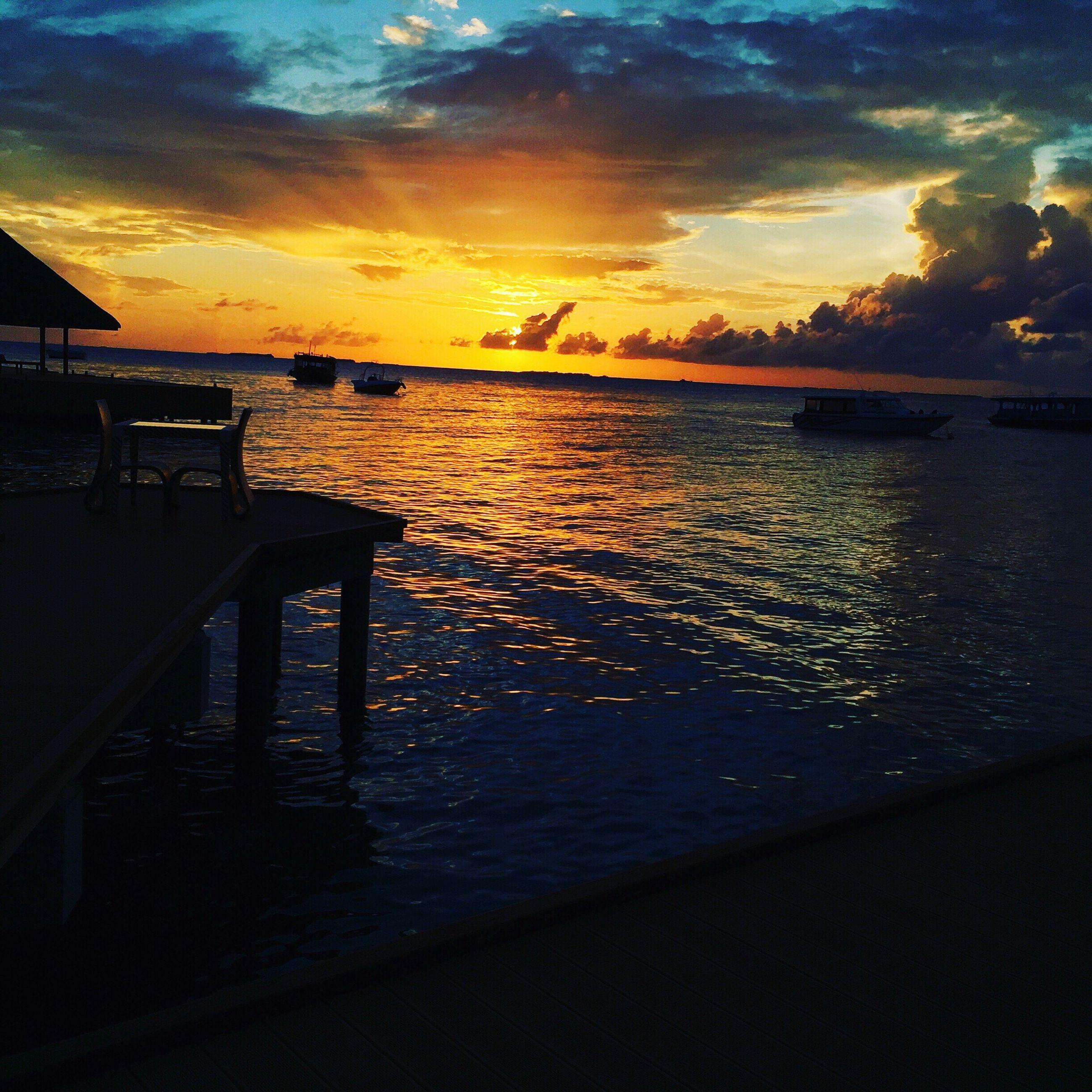 sunset, water, scenics, tranquil scene, sea, tranquility, idyllic, orange color, beauty in nature, sky, reflection, cloud - sky, pier, dramatic sky, rippled, nature, cloud, remote, moody sky, outdoors, calm, majestic, no people, ocean, romantic sky, coastline, non-urban scene