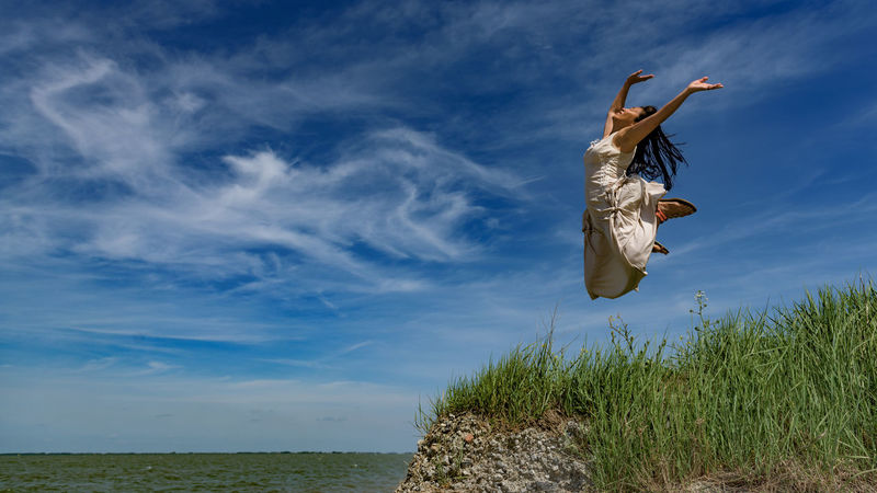 """On the edge of Zeeland, where sea and land meet, a woman jumps high in a blue sky washed with clouds. (Nikon D810 ƒ/5.0 24mm 1/1250"""" iso 80) The Great Outdoors - 2016 EyeEm Awards Let Your Hair Down Art Beach Beauty In Nature Blue Chinese Cloudscape Coast Creativity Easter Ready Ethnic Grass Happy Joy Jump Jumping Blue Wave Nature Outdoors The Essence Of Summer One Person Woman Need For Speed Www.benjaminvanderspek.com"""