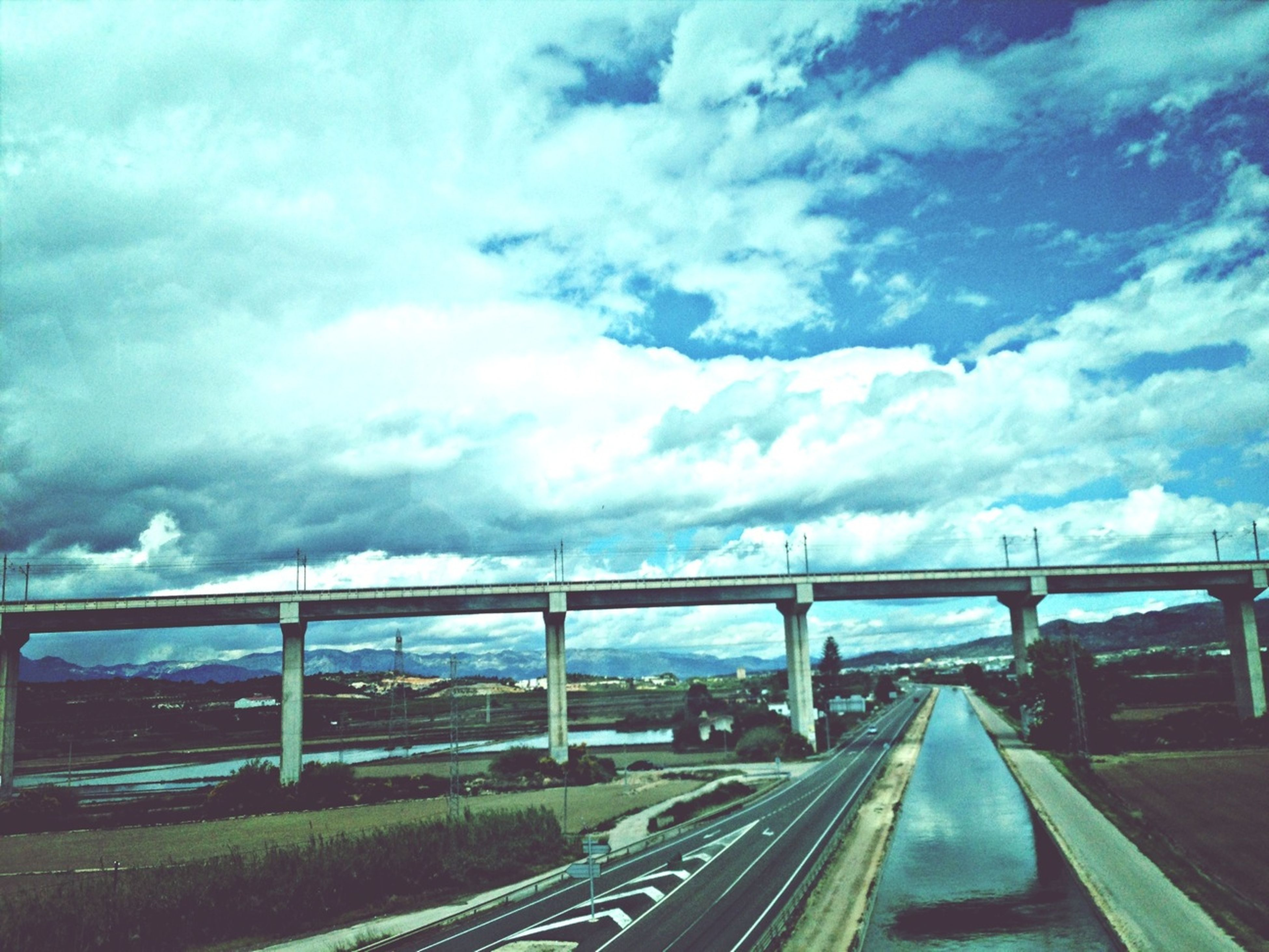 transportation, sky, cloud - sky, cloudy, road, cloud, the way forward, mode of transport, weather, land vehicle, car, diminishing perspective, railroad track, rail transportation, railing, overcast, connection, highway, road marking, vanishing point