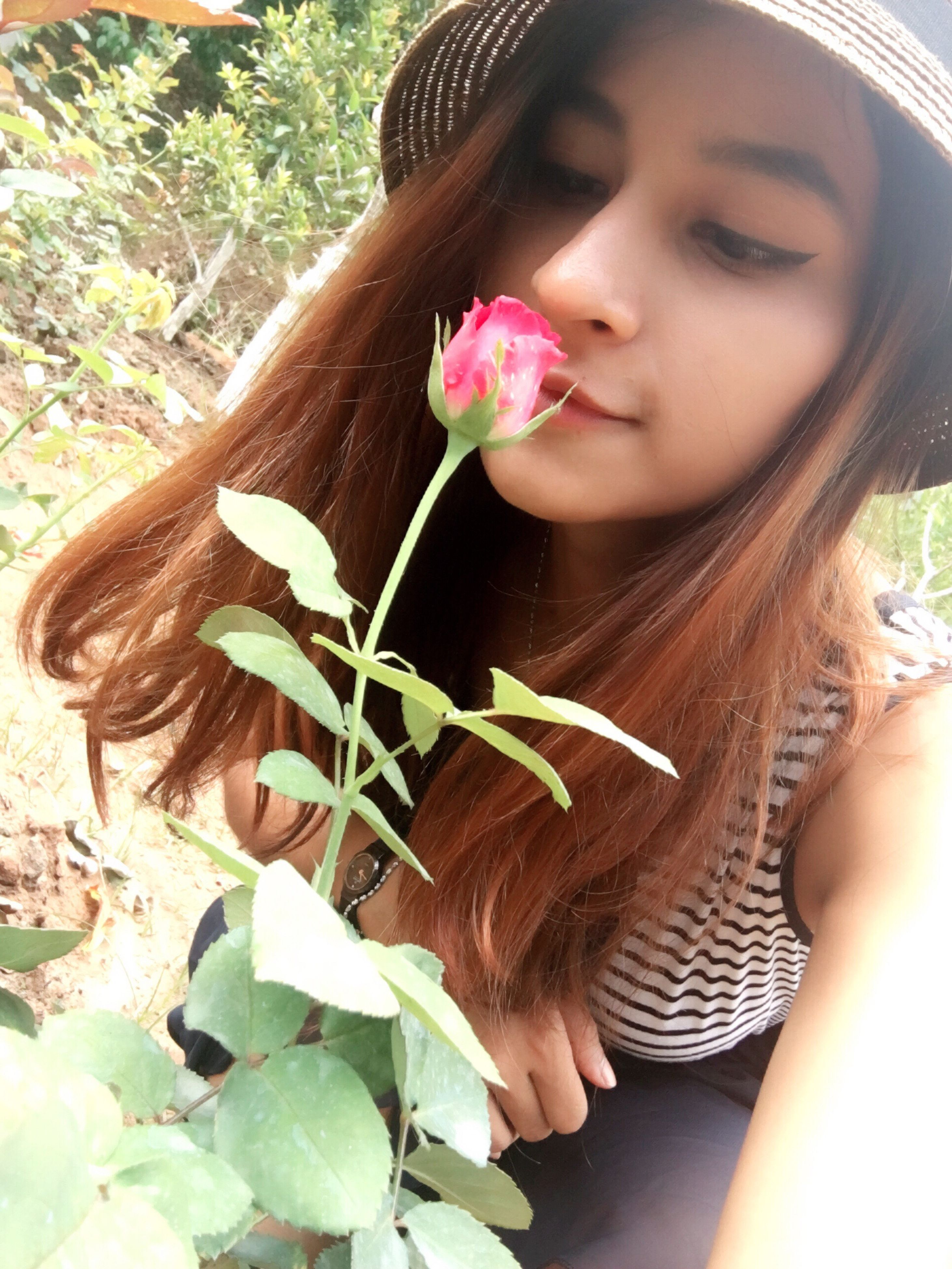 flower, person, young women, fragility, lifestyles, freshness, young adult, leisure activity, casual clothing, holding, girls, childhood, long hair, front view, elementary age, plant, pink color
