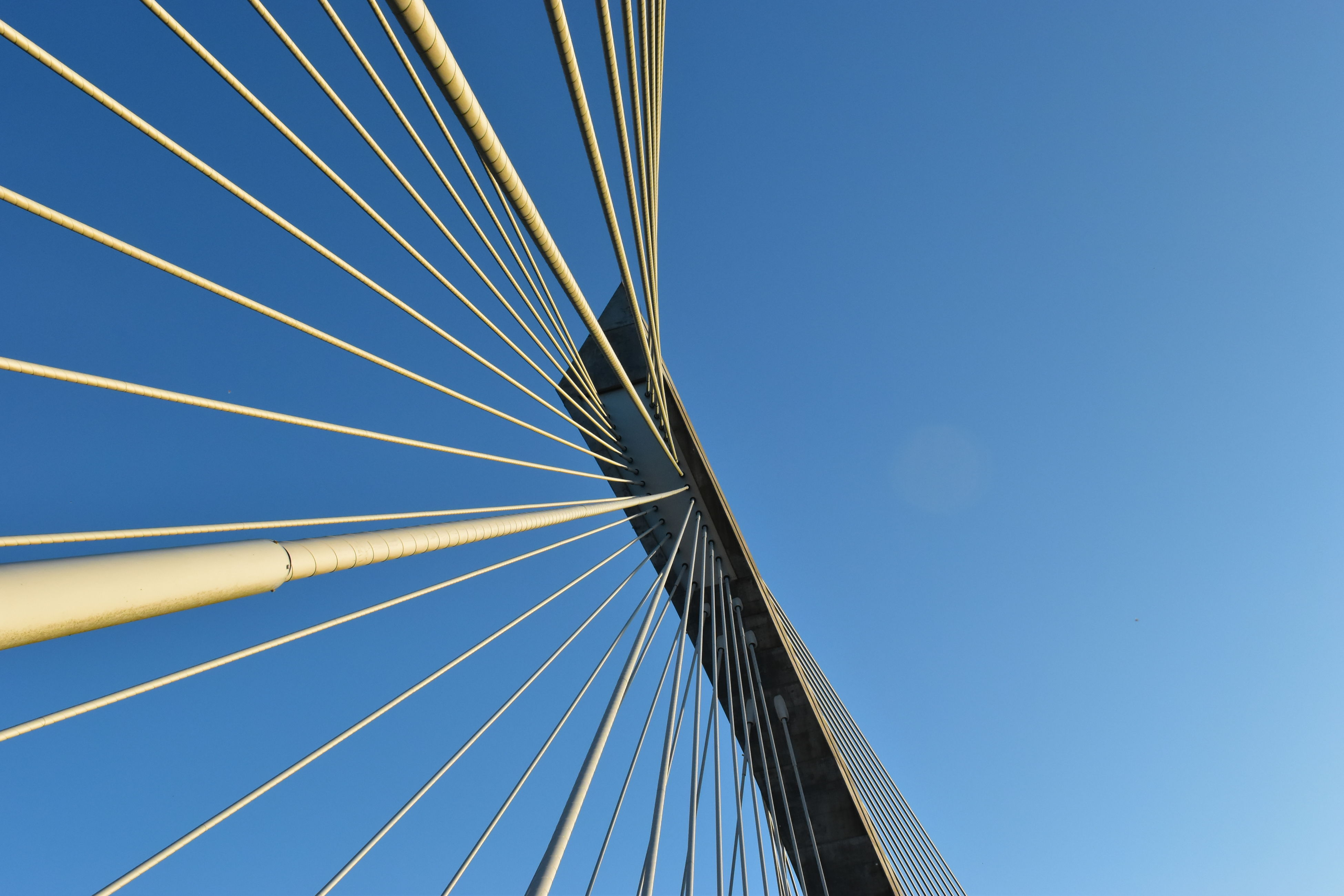 low angle view, clear sky, blue, sky, connection, built structure, transportation, no people, outdoors, architecture, day, bridge - man made structure, suspension bridge