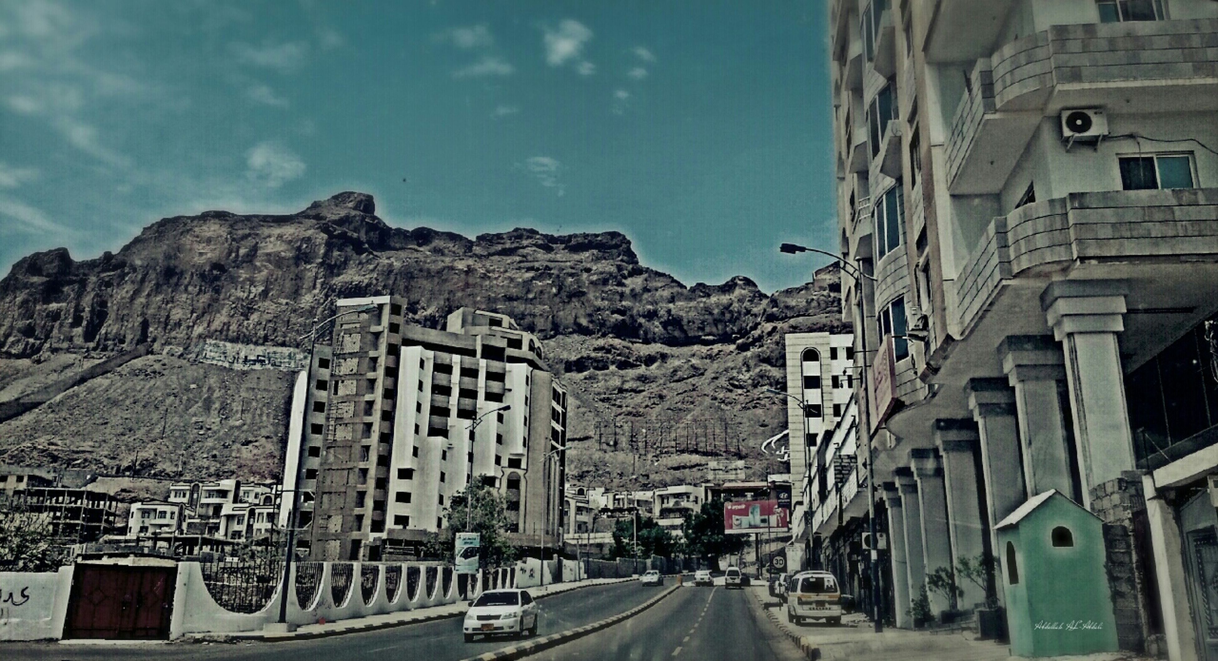 architecture, transportation, building exterior, car, built structure, land vehicle, road, mode of transport, street, mountain, sky, the way forward, city, residential building, outdoors, incidental people, vehicle, building, day, travel