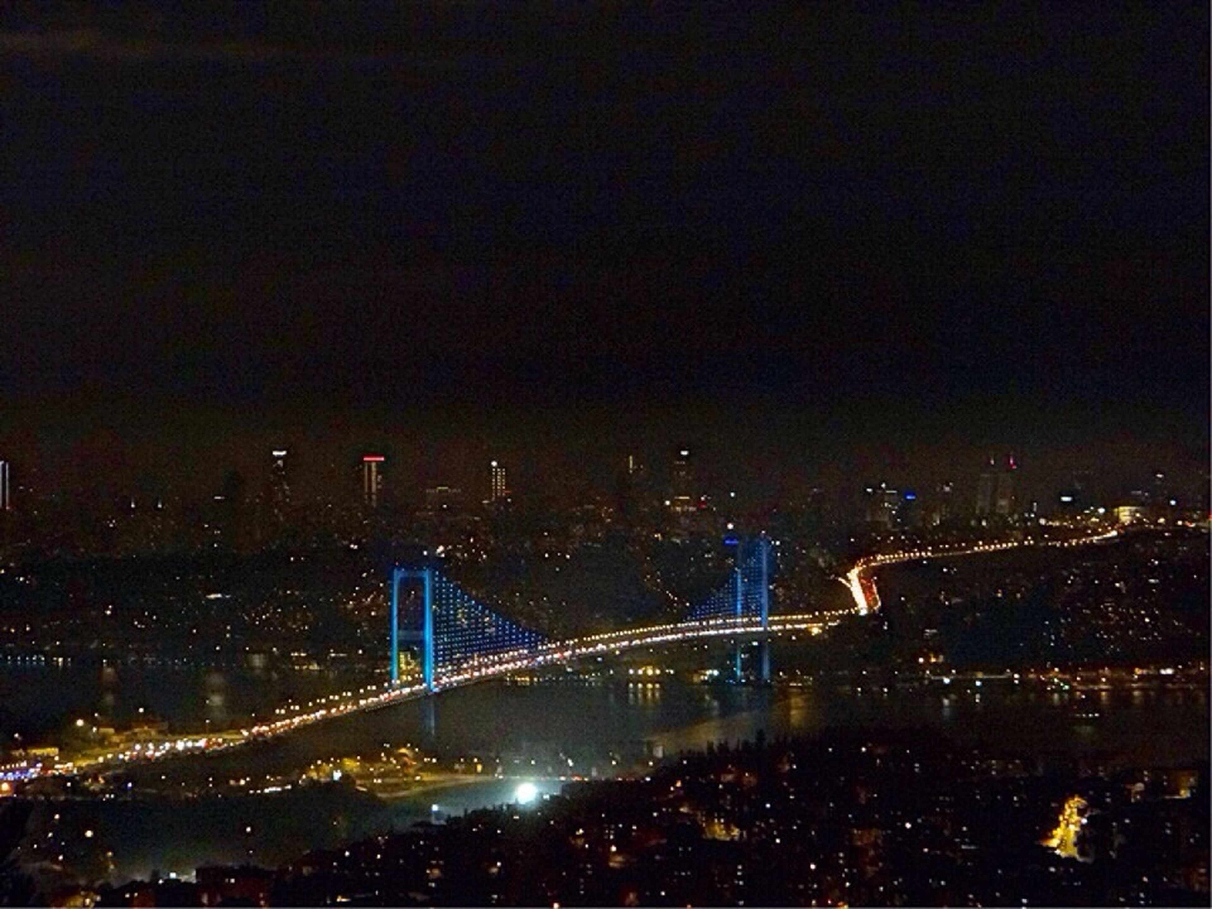 night, illuminated, city, architecture, built structure, bridge - man made structure, connection, cityscape, transportation, water, copy space, river, suspension bridge, bridge, building exterior, high angle view, sky, engineering, city life, travel destinations