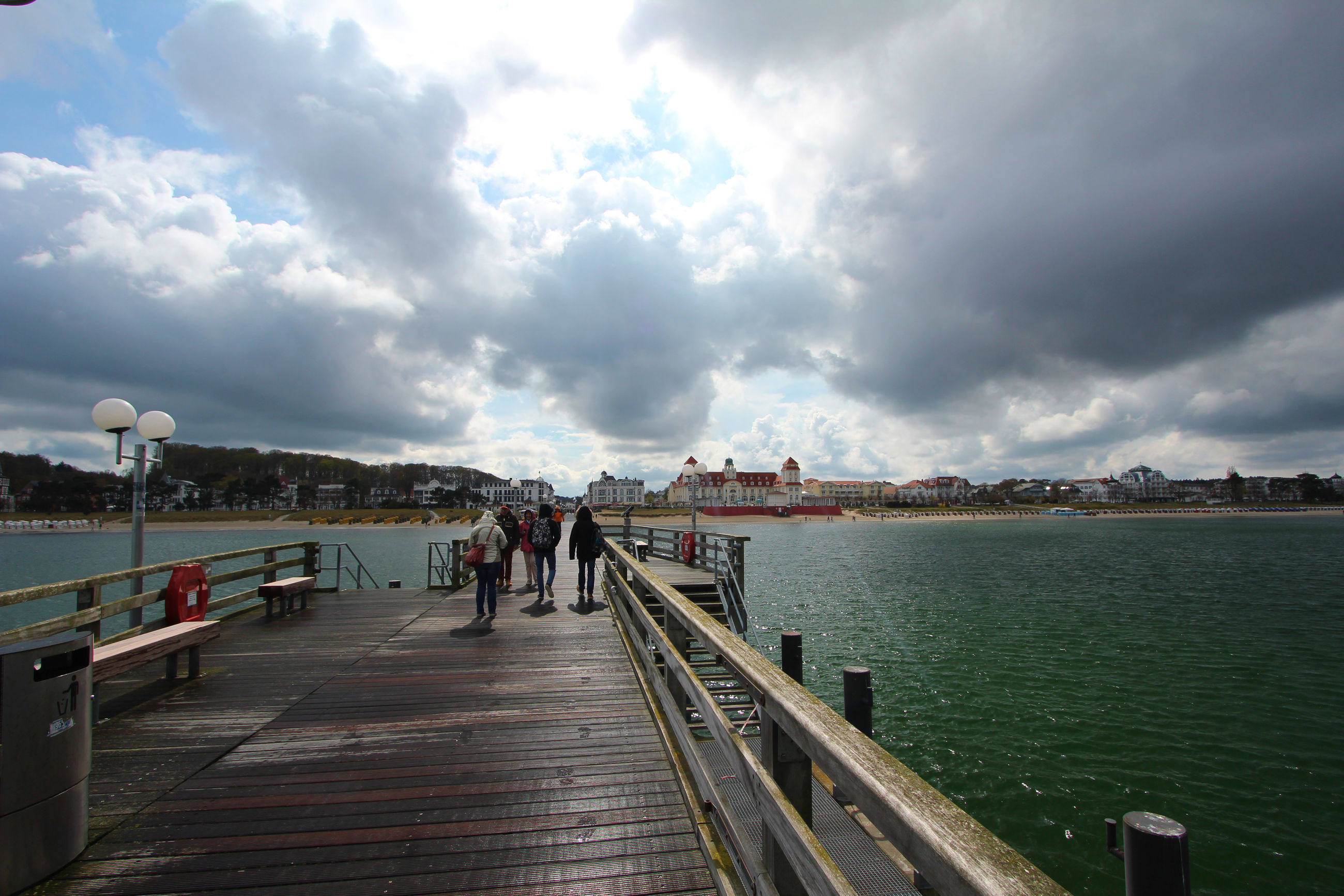sky, water, the way forward, cloud - sky, sea, built structure, pier, cloudy, railing, men, architecture, cloud, walking, lifestyles, diminishing perspective, person, leisure activity, building exterior, incidental people