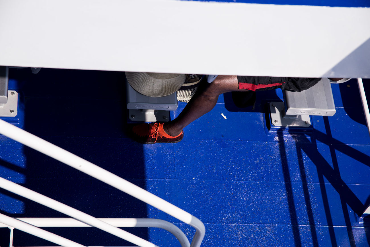 On a boat to Ko Phangan island in Gulf of Thailand Abstract Boat Contrast Cruise Day Ferry Gulf Of Thailand Holiday Ko Phangan Leg Men Men Only Sea Shadows Ship South East Asia Street Photography Streetphoto Streetphoto_color Streetphotography Summer Thailand Tourism Tourists Trainers