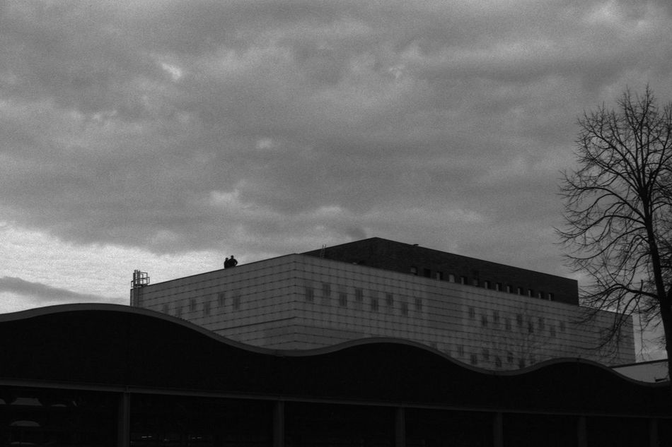 People on the Roof 35mm Film Analogue Photography Architecture Black & White Building City Clouds Contrast Fomapan100 People Rodinal Roof Sky Street Scene Streetphotography Together Tree Urban Working