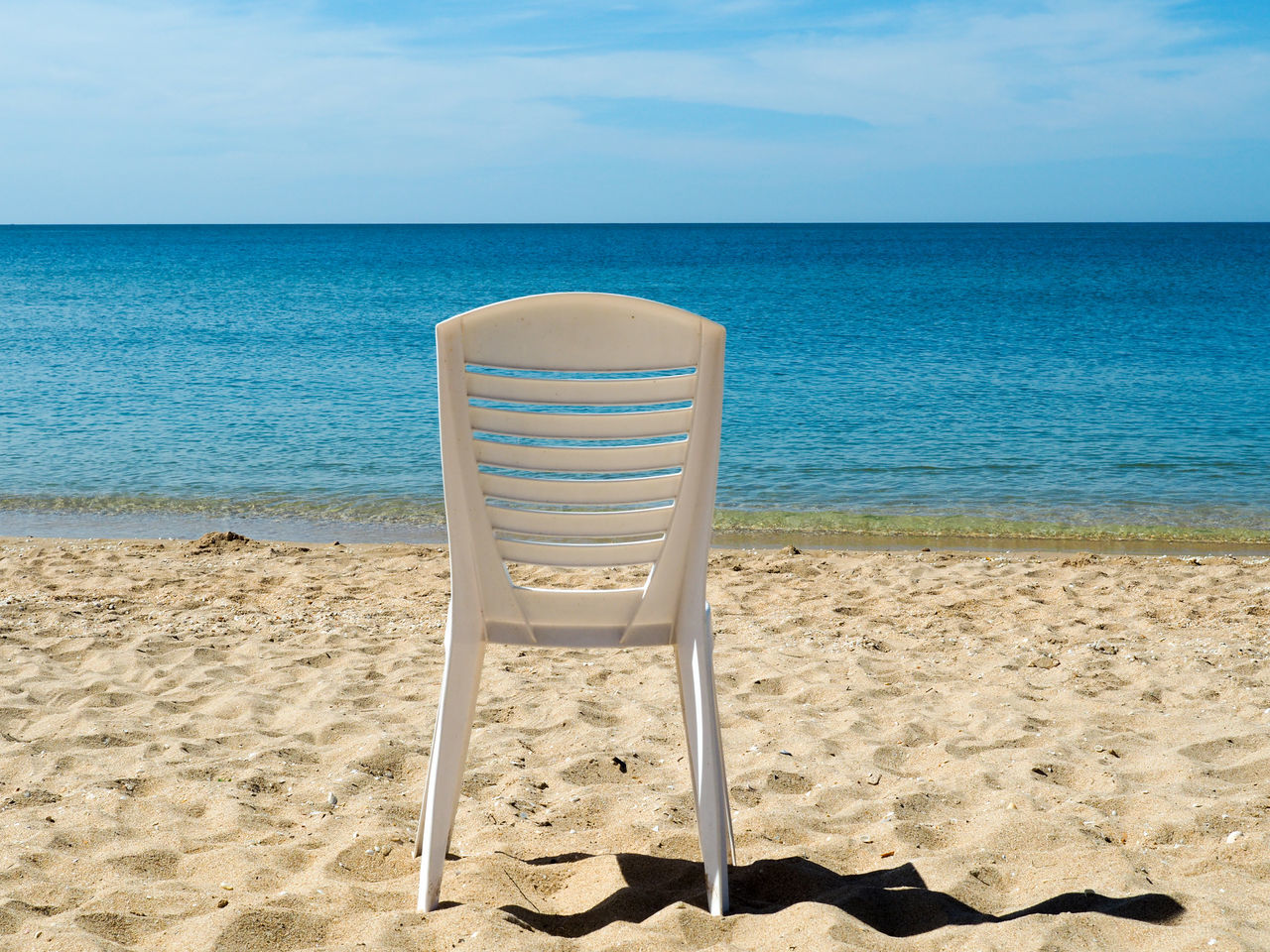 sea, beach, sand, horizon over water, water, nature, sky, tranquil scene, tranquility, beauty in nature, chair, scenics, no people, day, vacations, sunlight, outdoors