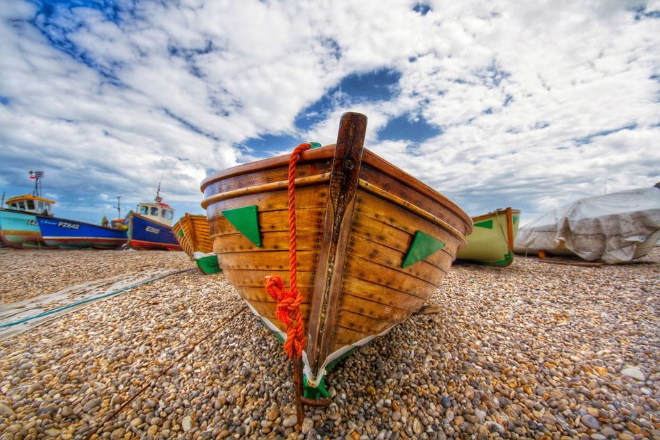Wooden fishing boats on a pebble beach Fishing Fishing Boat Boats Wooden Boat Beach Pebble Beach Pebbles Beached Boat Moored Seaside Holiday Vacation Industry Unused DISUSED Dwindling