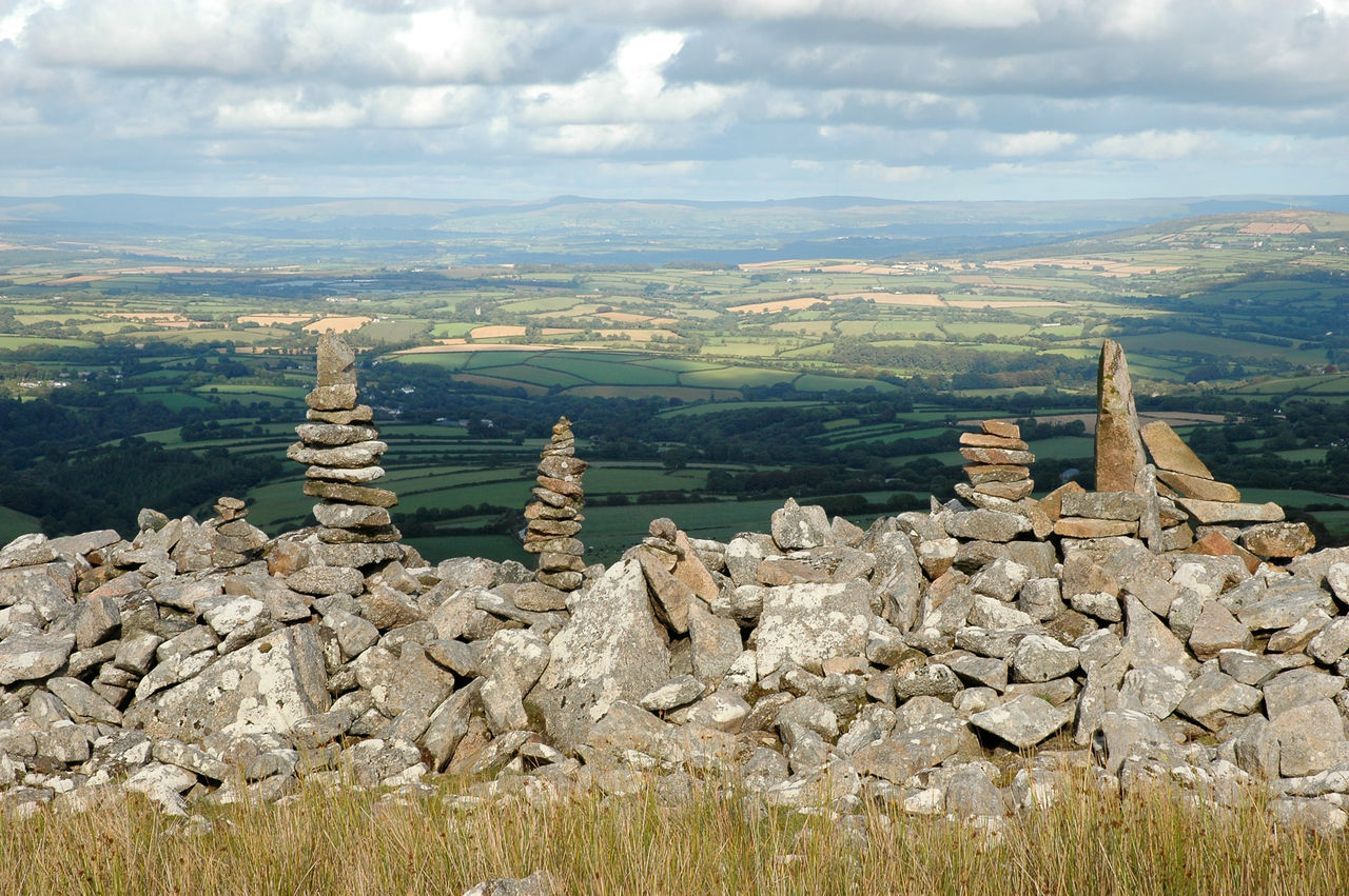 Stack Of Rocks On Landscape Against Cloudy Sky