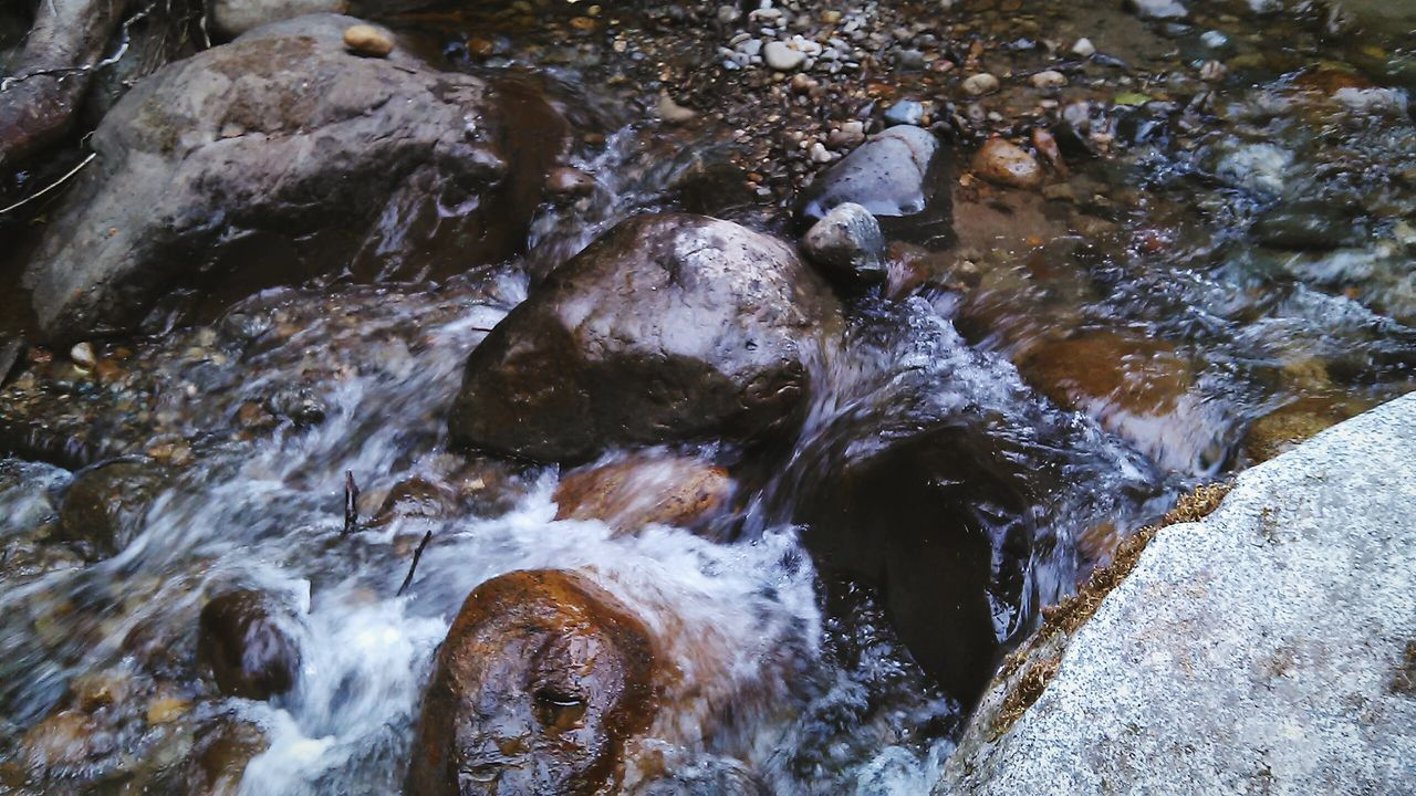 CLOSE-UP OF STREAM FLOWING THROUGH ROCKS