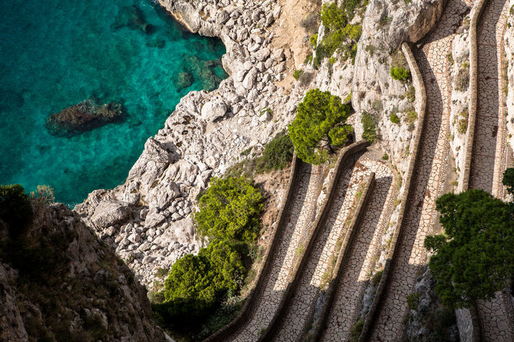 Capri, Italy, Via Krupp winds along the slope, leading to the sea underneath. Beauty In Nature Capri Cliff Geometric Architecture Holiday Italy Krupp Landscape Lines Natural Pattern Outdoors Panorama Path Pathway Sea Sea And Rocks Textured  Tranquility Traveling Tree Vía Krupp Walkway Market Reviewers' Top Picks