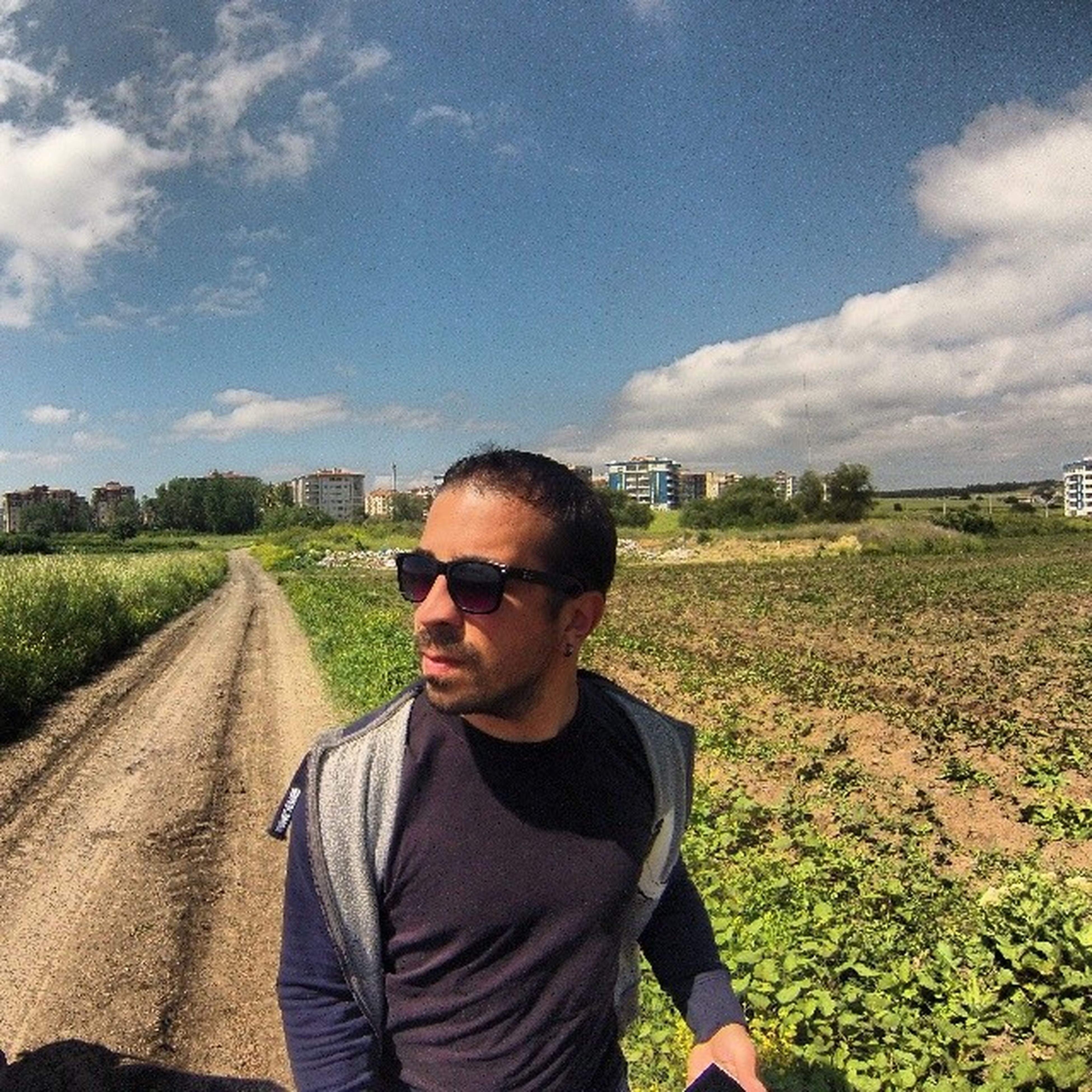 lifestyles, sky, person, leisure activity, casual clothing, young adult, looking at camera, portrait, field, young men, smiling, cloud - sky, sunglasses, front view, landscape, headshot, standing, head and shoulders