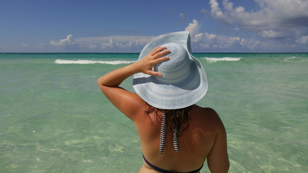 Rear View Of Woman With Hat Standing In Sea Against Sky On Sunny Day