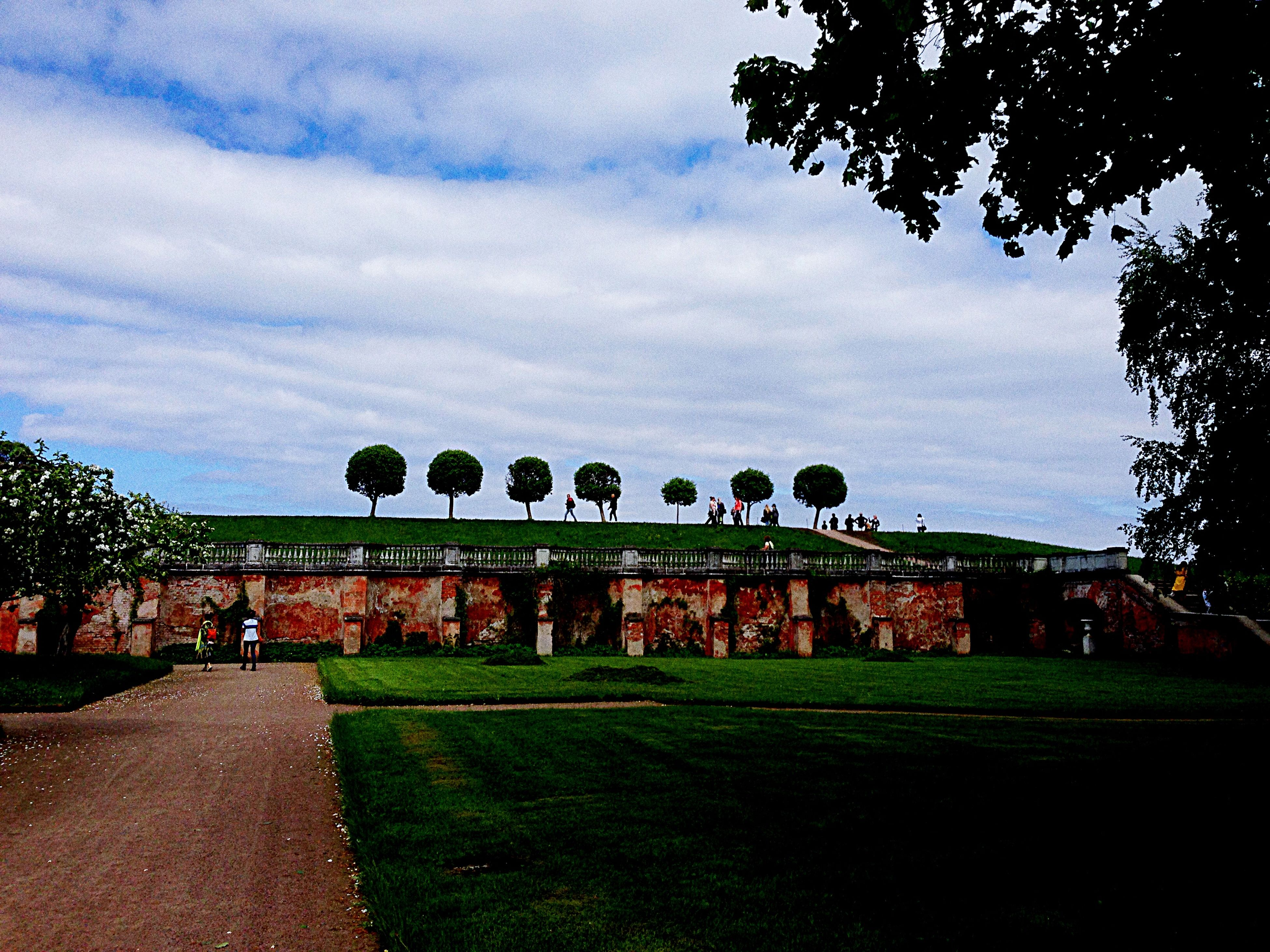 sky, grass, tree, architecture, built structure, cloud - sky, building exterior, cloudy, green color, famous place, lawn, history, travel destinations, cloud, tourism, travel, park - man made space, outdoors, day, the past