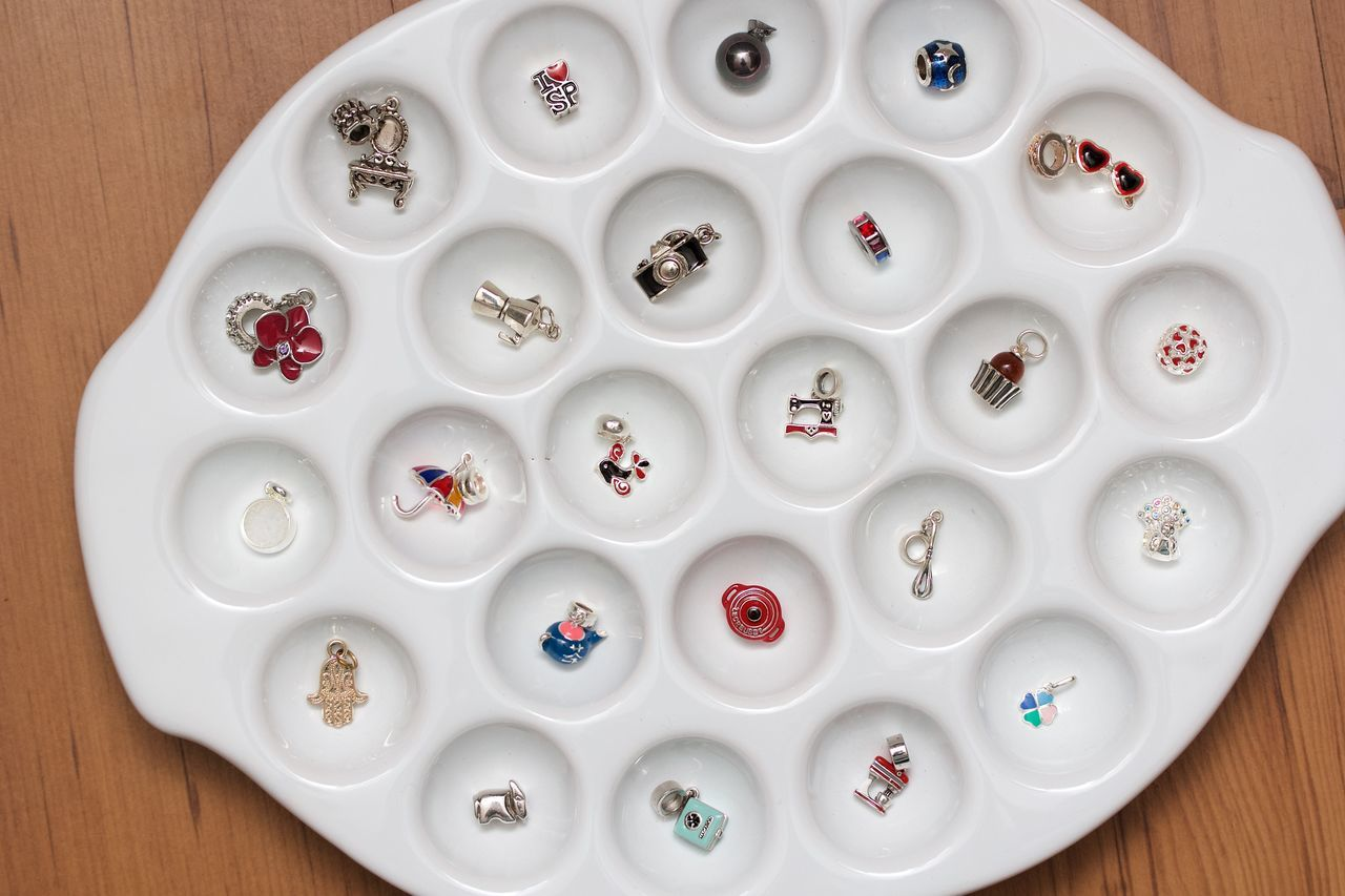 pandora sterling pendants in a white plate Bracelet Large Group Of Objects Miniature No People Pandora Pendant Silver  Sterling White Color