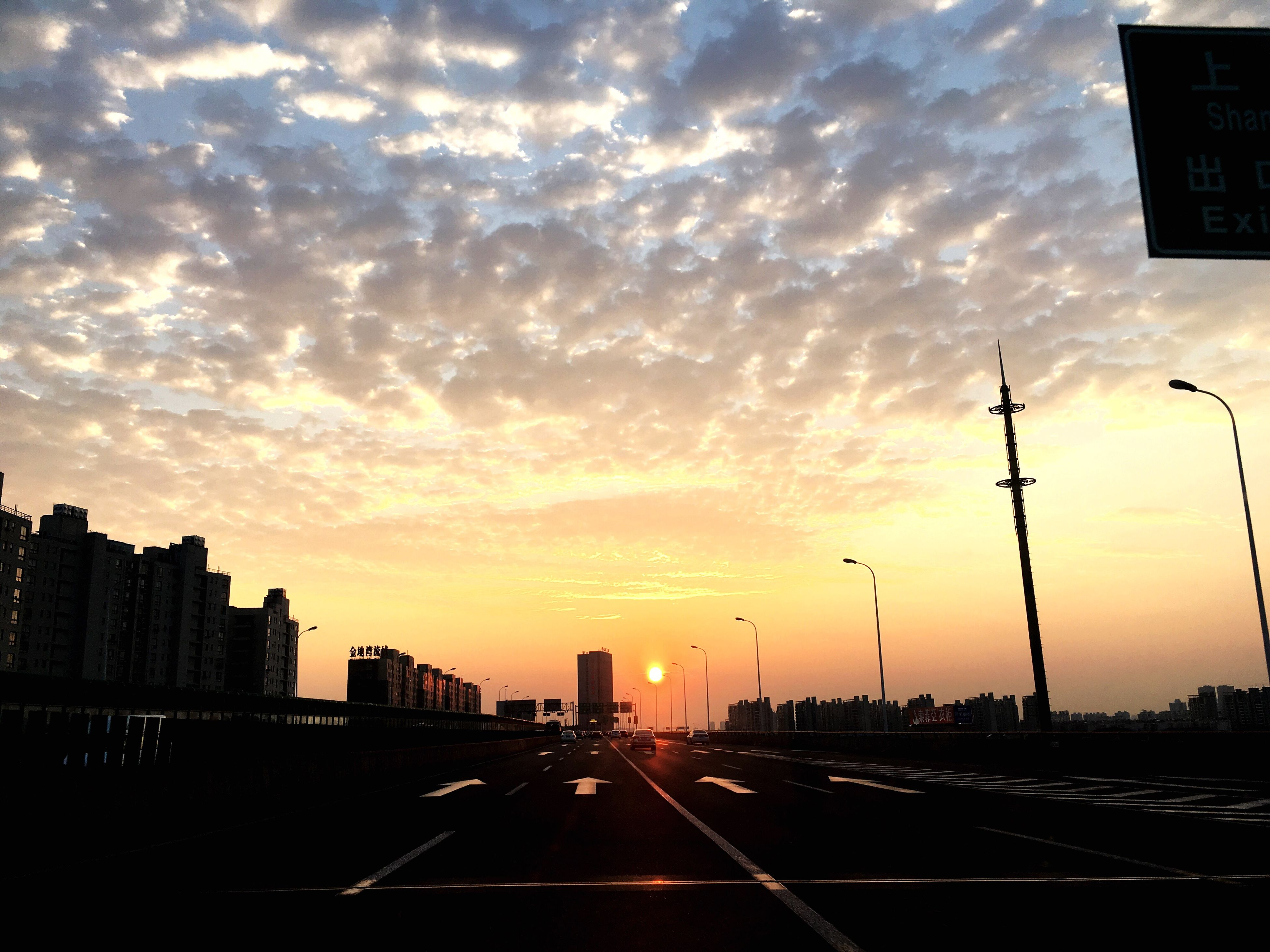 sunset, transportation, building exterior, city, sky, architecture, built structure, road, silhouette, cloud - sky, car, orange color, street, street light, the way forward, land vehicle, traffic, road marking, mode of transport, cloud
