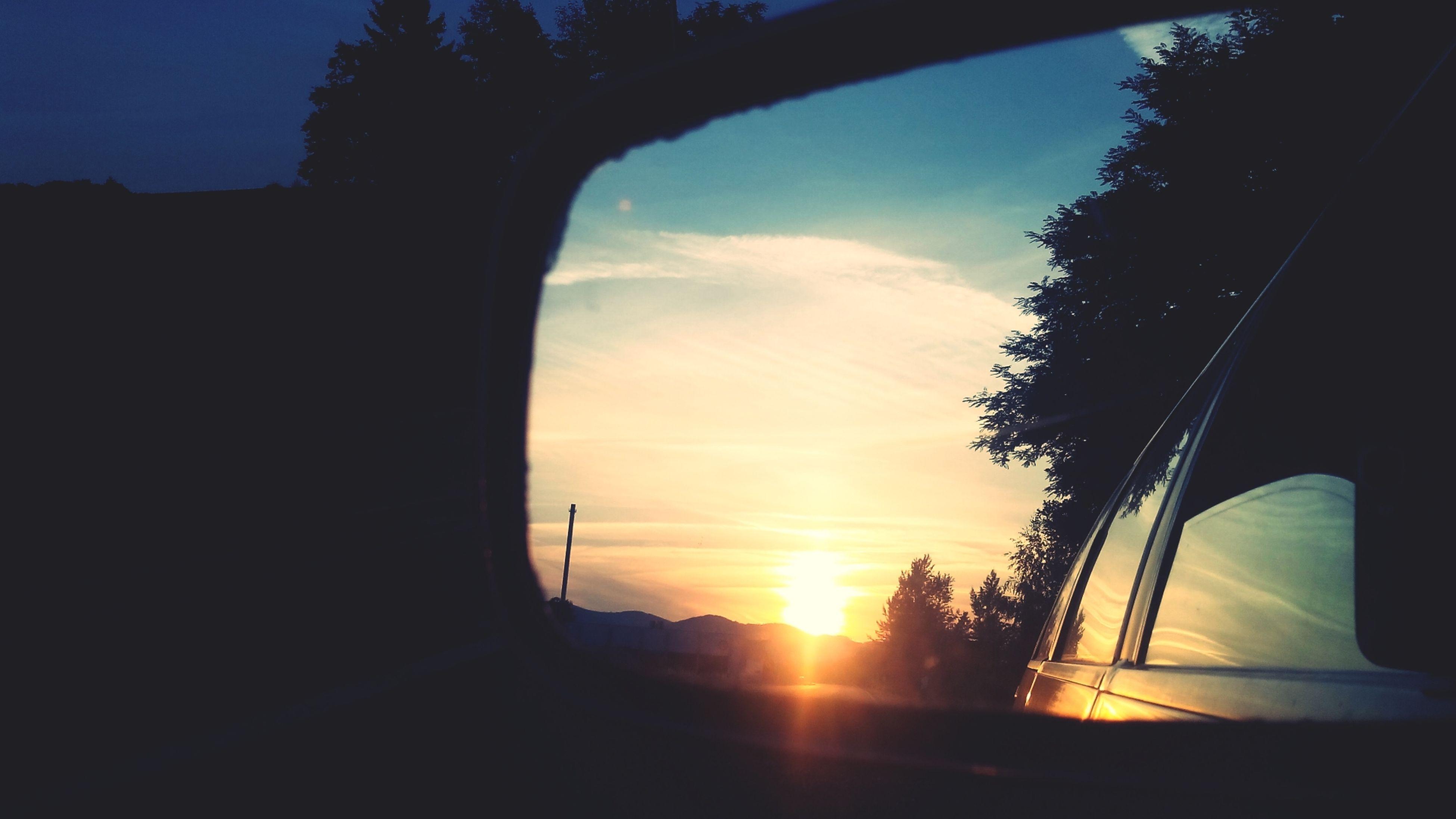 sunset, silhouette, sun, sky, transportation, car, tree, sunlight, mode of transport, land vehicle, road, orange color, beauty in nature, nature, sunbeam, cloud, scenics, tranquility, cloud - sky, vehicle interior
