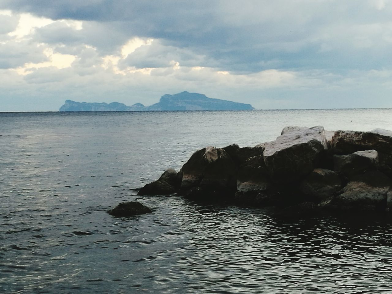 sea, water, tranquility, scenics, nature, beauty in nature, sky, tranquil scene, rock - object, no people, waterfront, outdoors, cloud - sky, day, horizon over water
